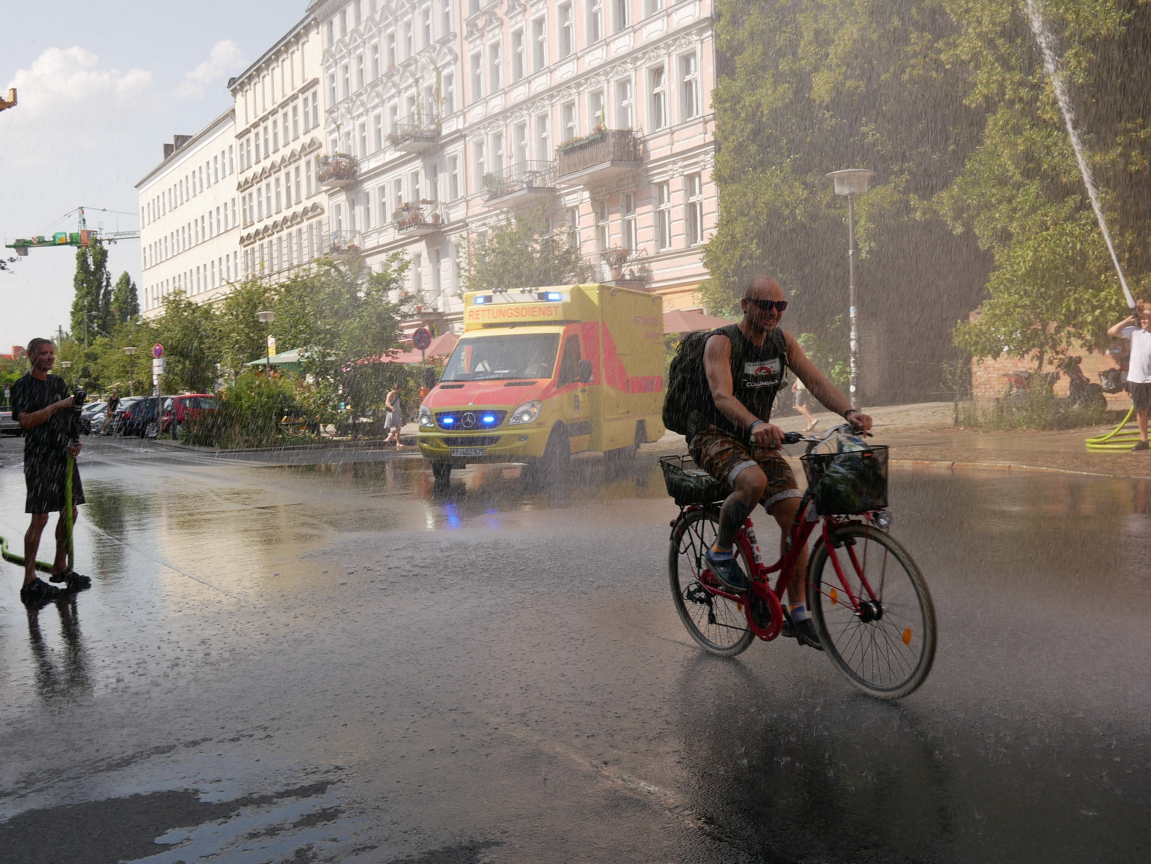 Firefighters blast water in Berlin in mid-August, providing relief from the heat. This is among the few ways to cool off in a city with little air conditioning.