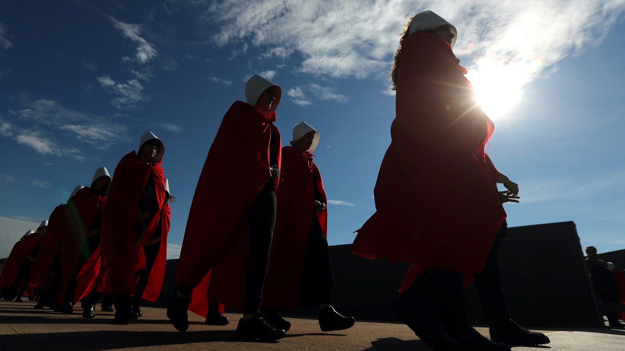 "Activists dressed up as characters from ""The Handmaid's Tale"" are shown back lit from a low perspective."