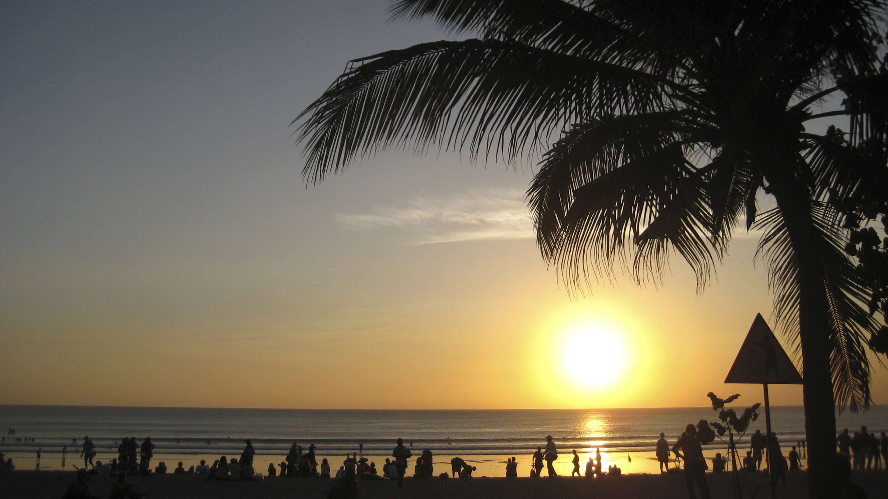Beachgoers watch the sun set at Kuta beach in Bali, Indonesia