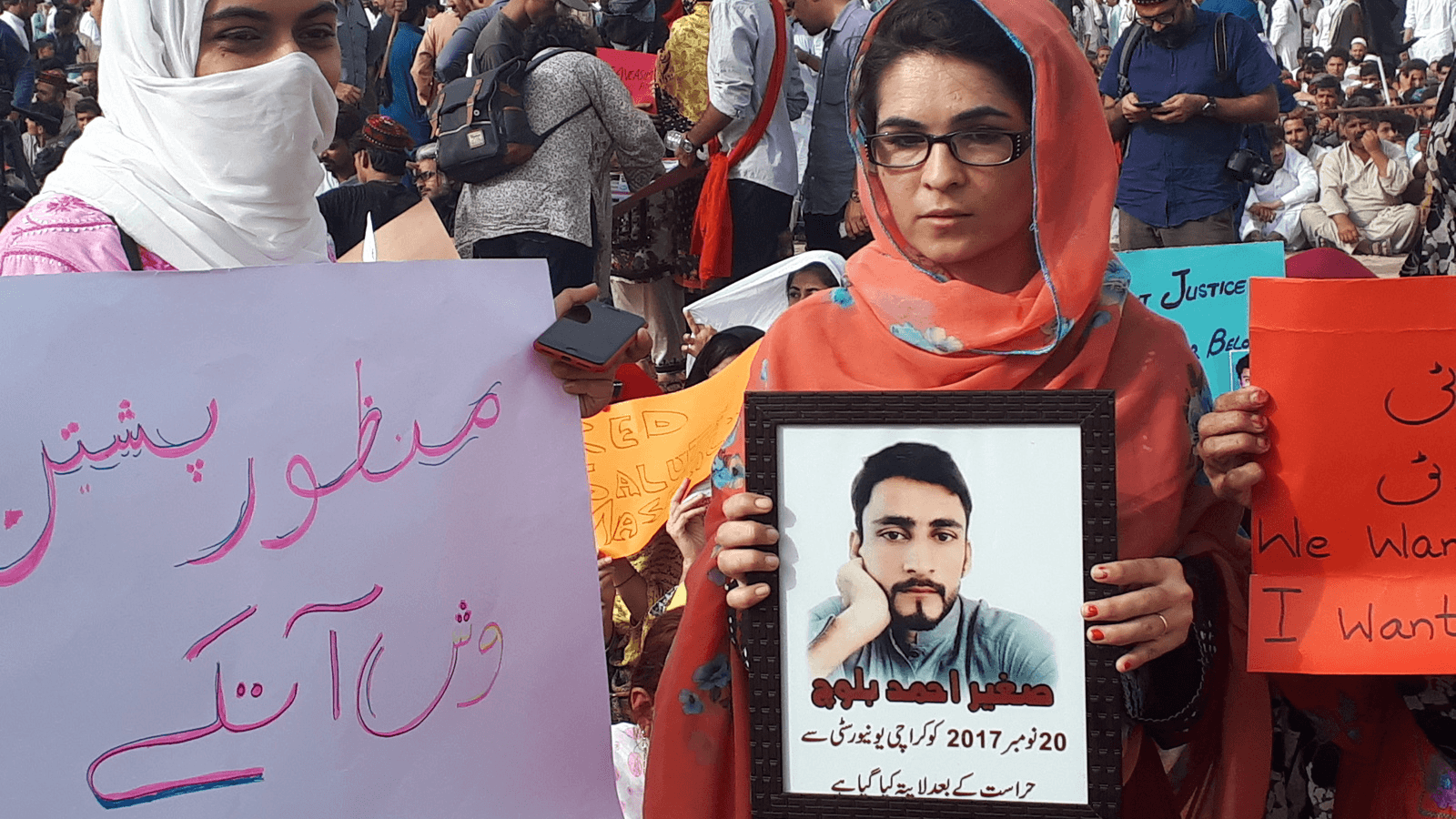 Pashtun women in Pakistan hold posters of their missing family members