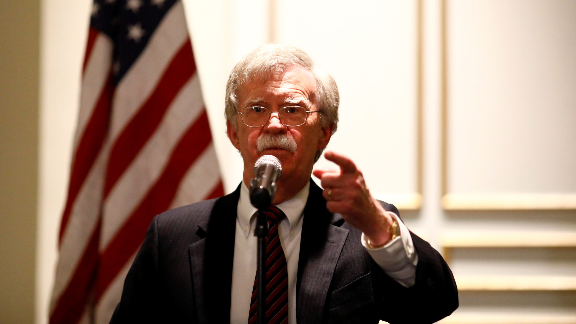 National Security Adviser John Bolton is shown at a microphone with the US flag behind him, speaking at a forum in Washington, DC, 2018.