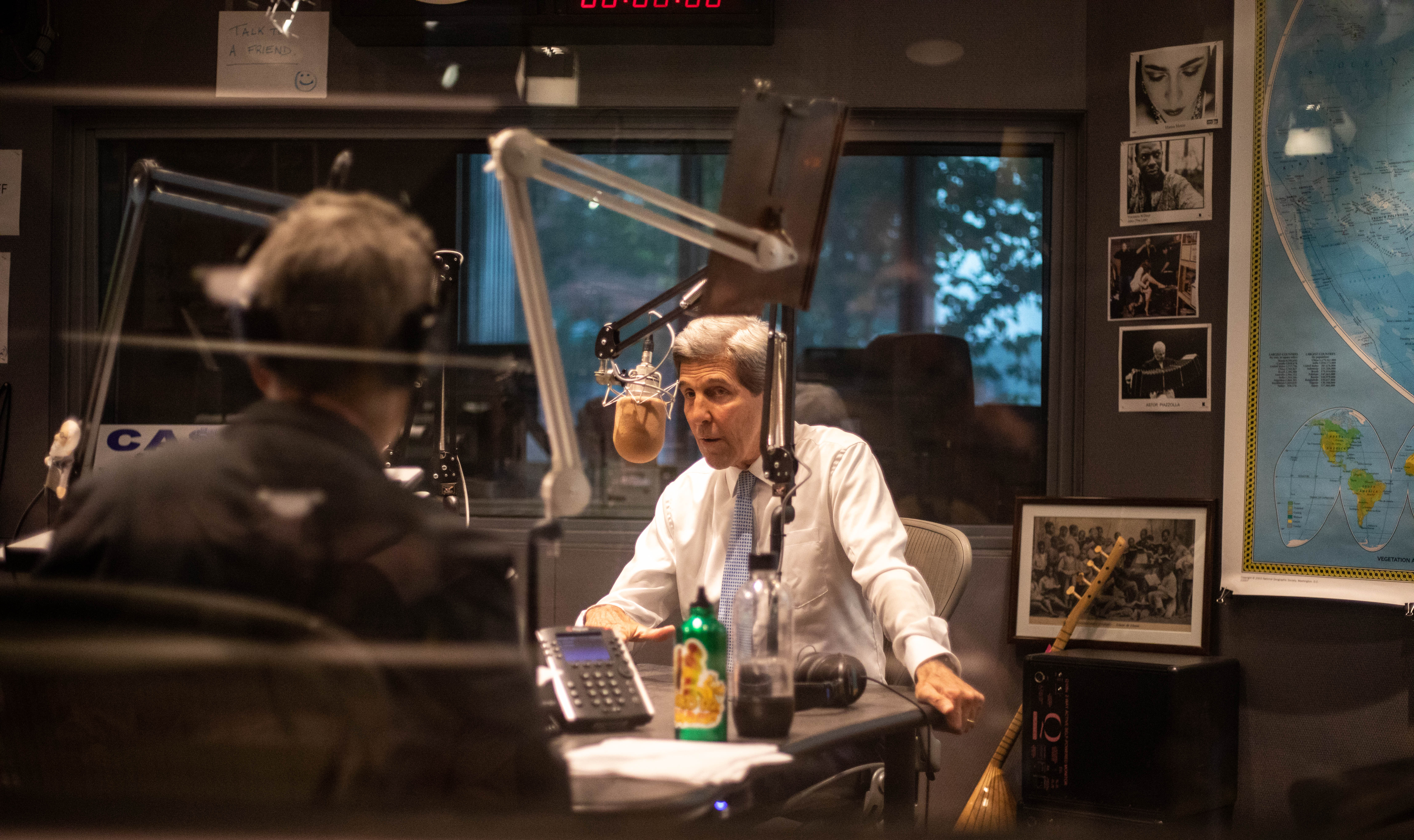 John Kerry stands behind the mic in The World studio