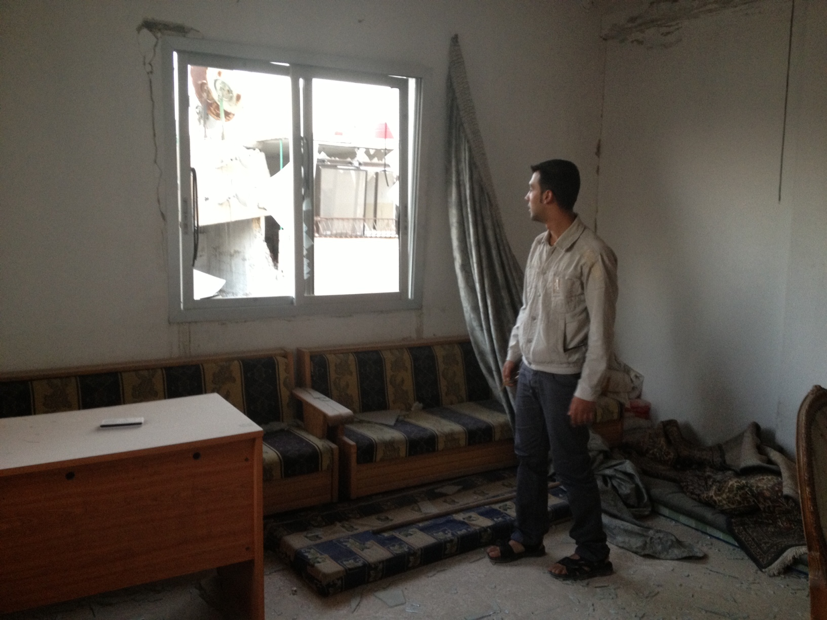 man looking out a broken window, surrounded by rubble
