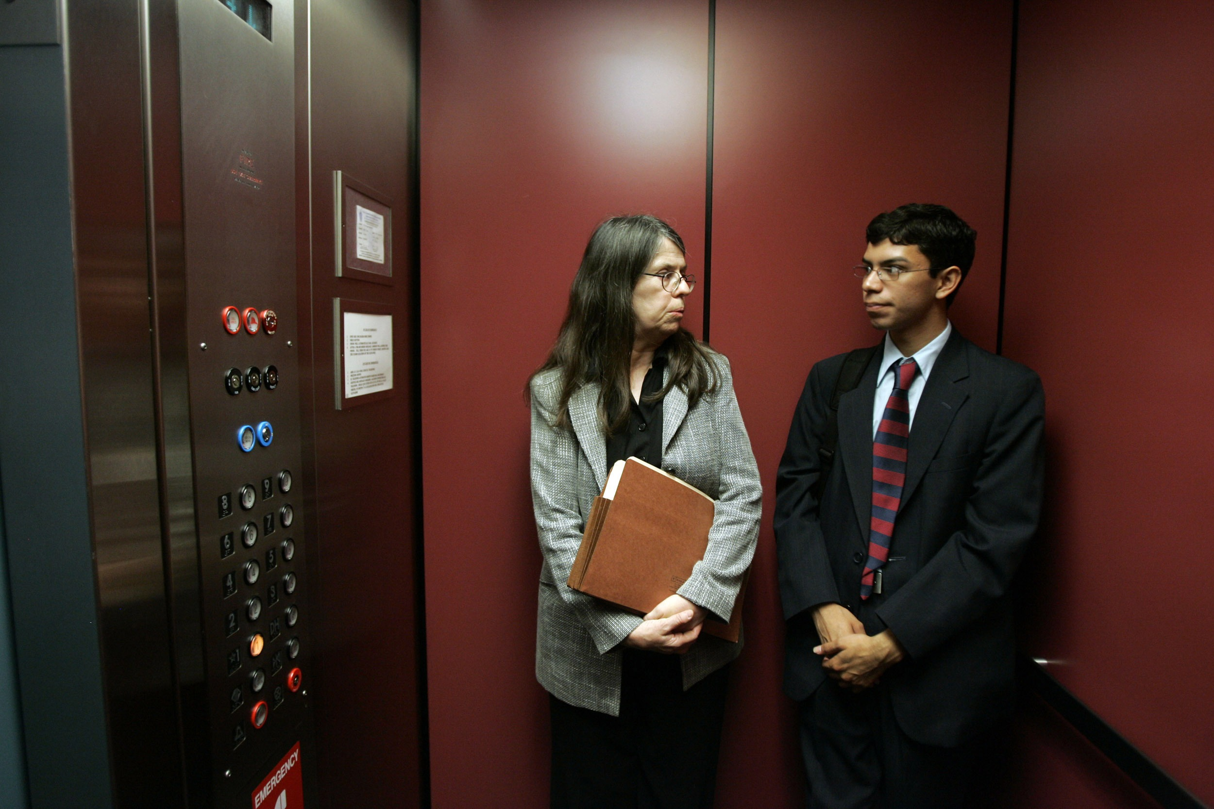Woman and young man in suit holding papers look at each other in elevator