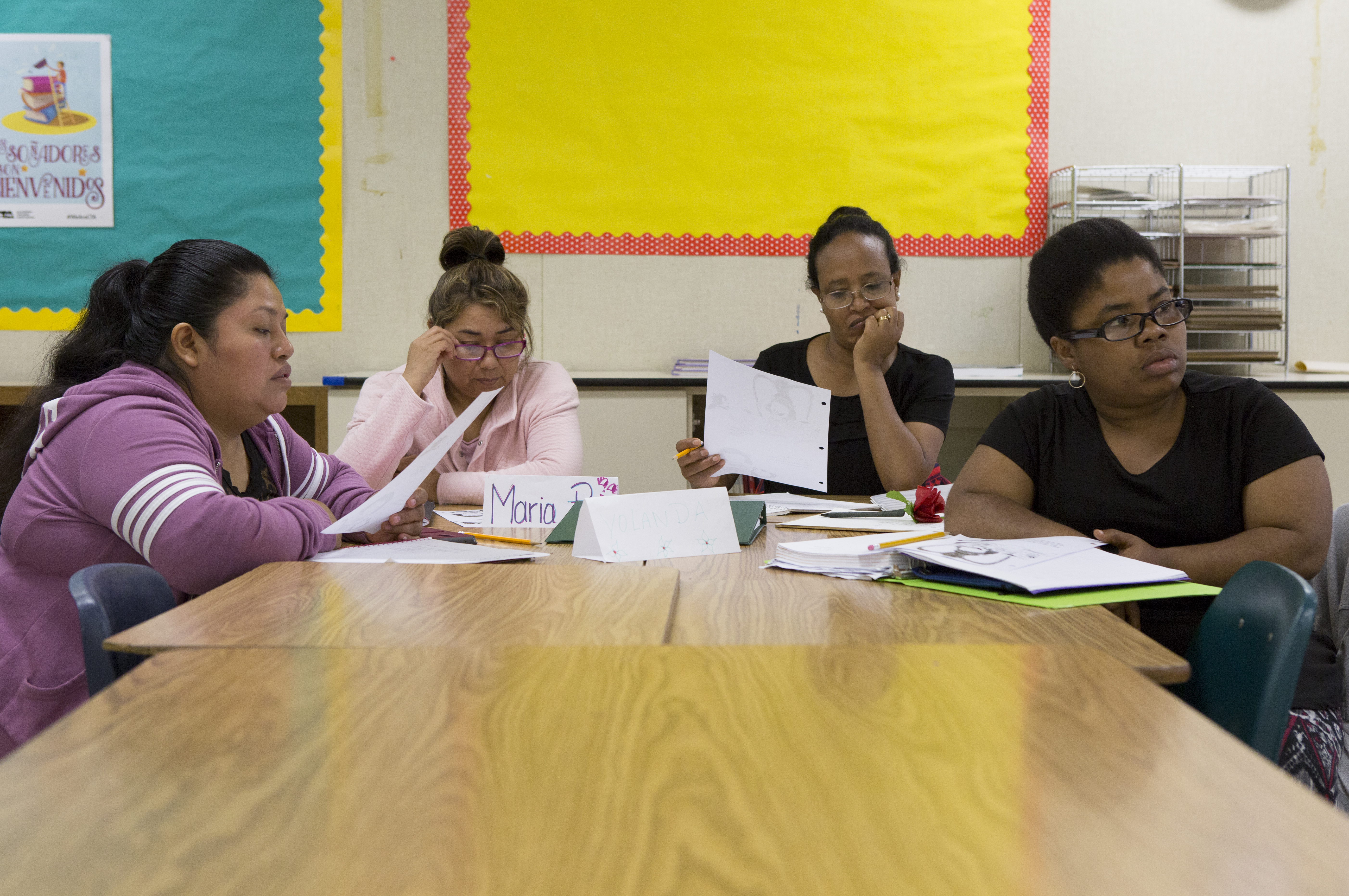 For women sit around elementary classroom tables, holding and reading papers