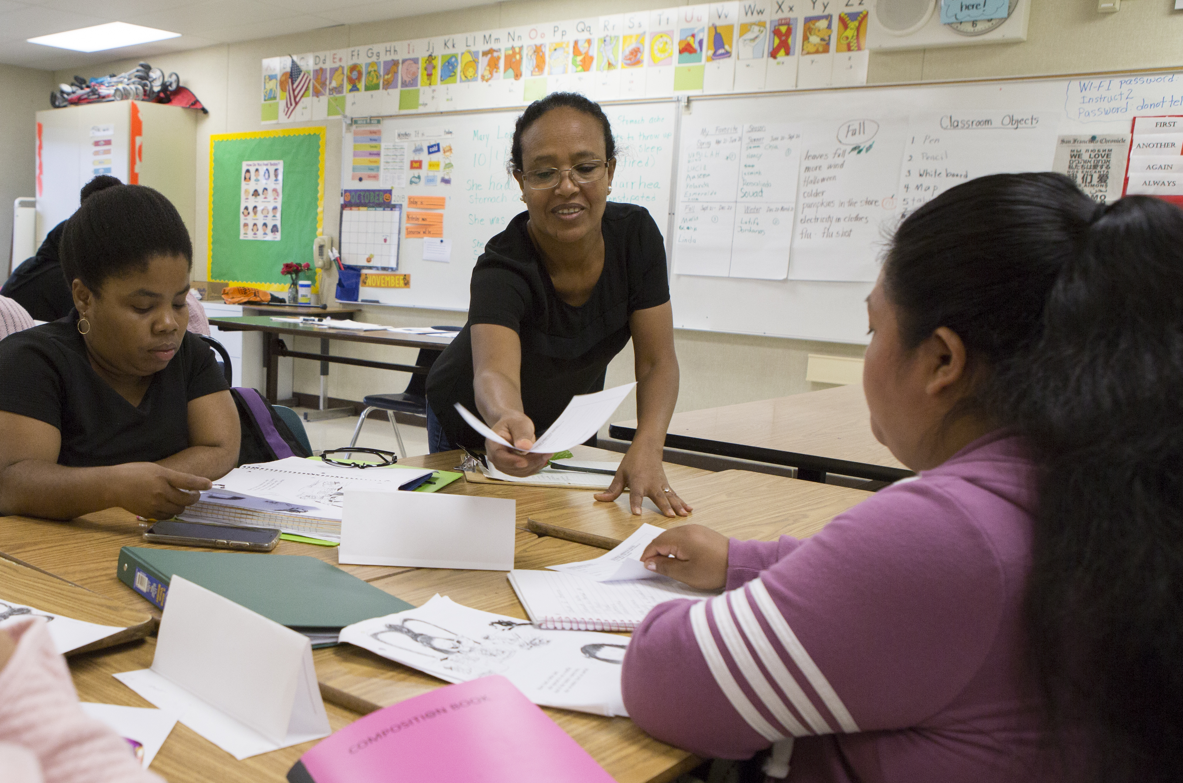 Woman leans over desks handing out paper, with two other women sitting around and white board in elemenatary school classroom behind them