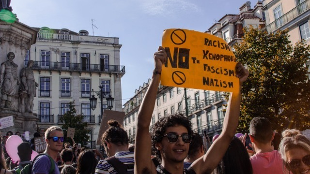 a man holds a protest sign in Lisbon