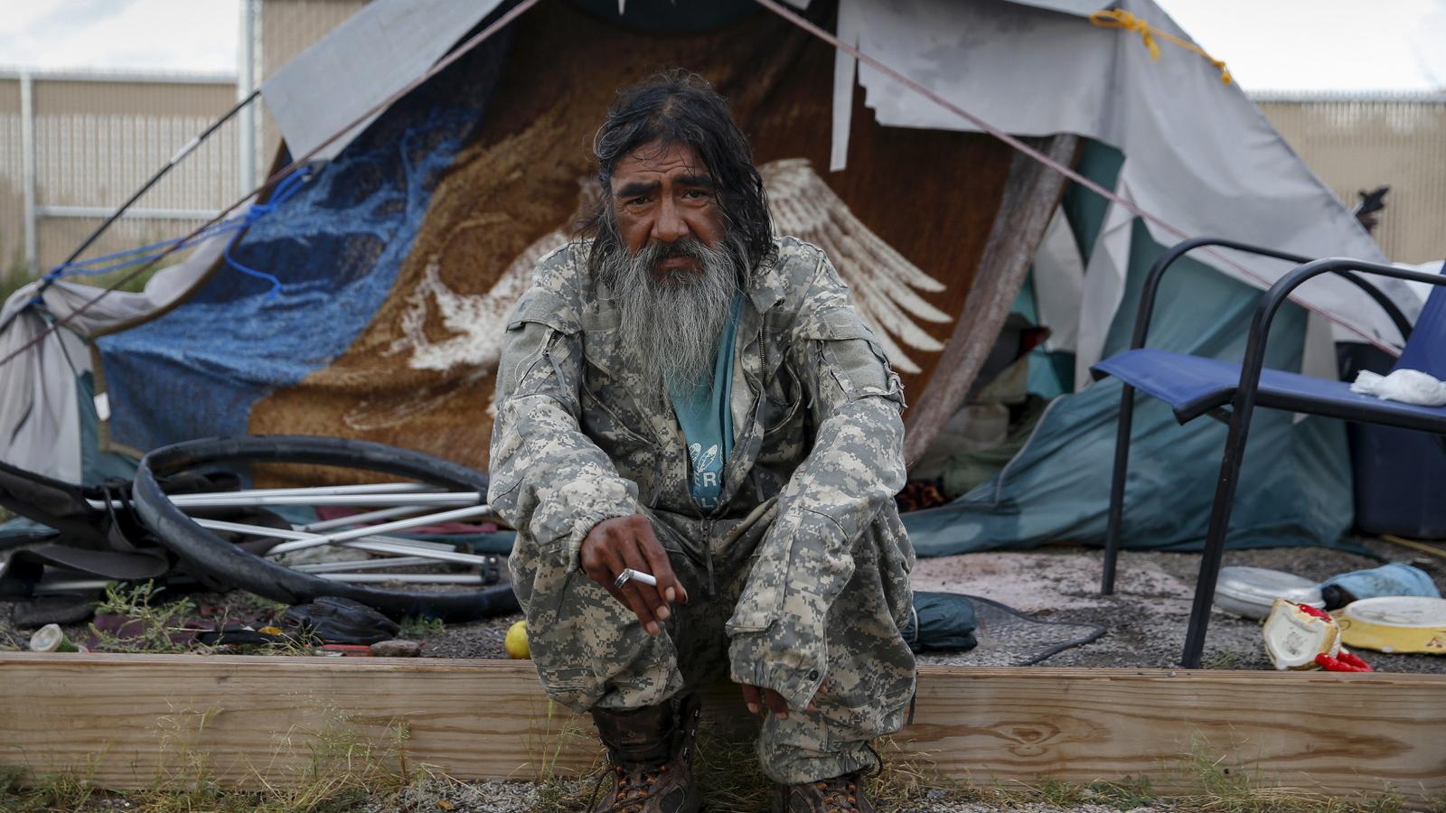 A bearded veteran sits outside a tent smoking a cigarette.