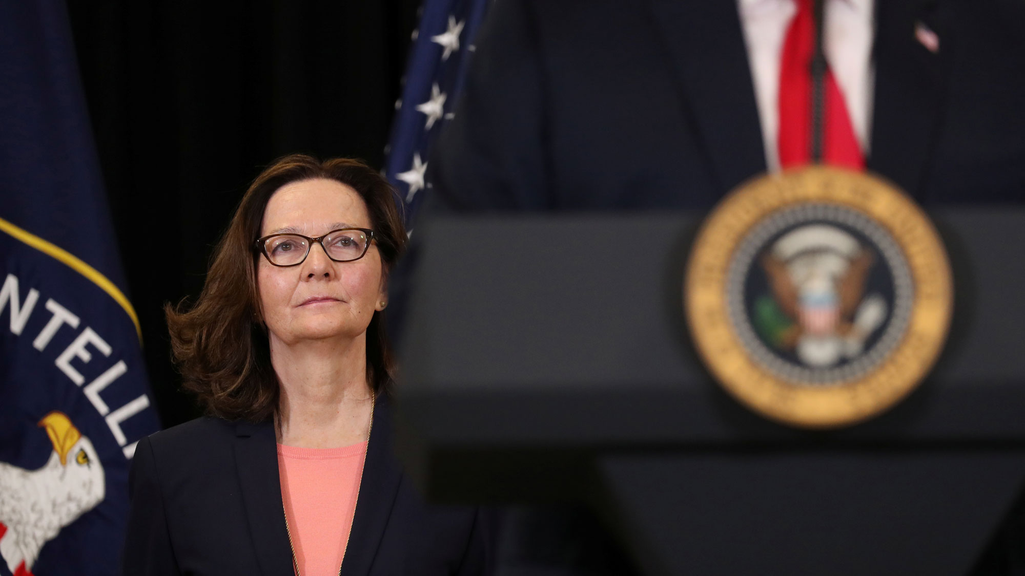 CIA Director Gina Haspel stands behind President Donald Trump with the Agency and US flags behind her.