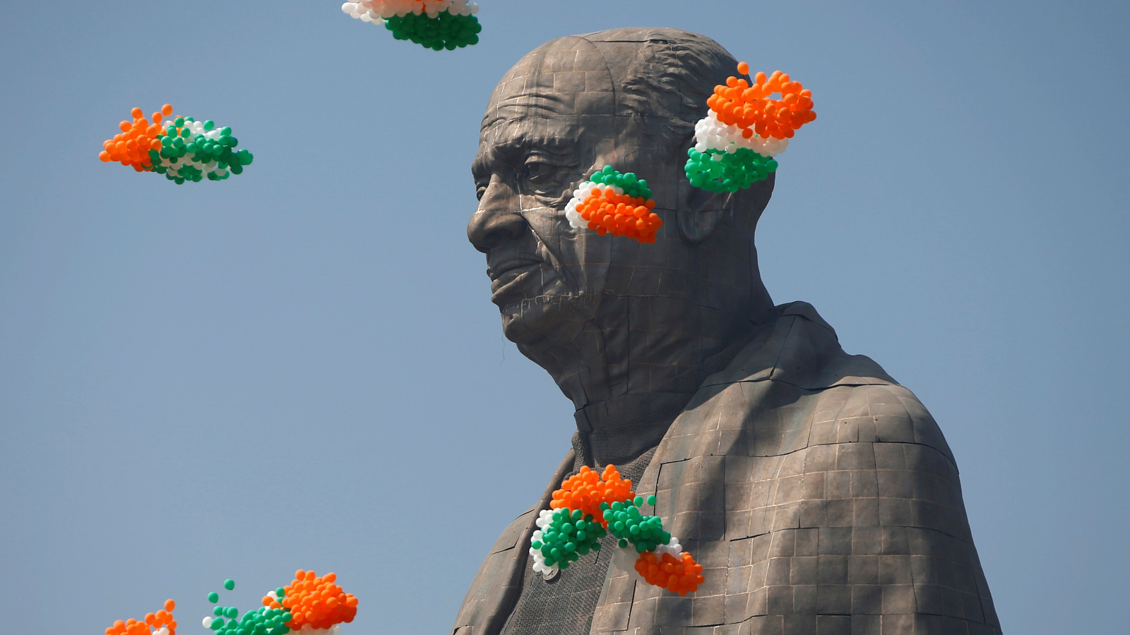 Indian tri-colored balloons fly around a statue head of Indian founding father Sardar Vallabhbhai Patel