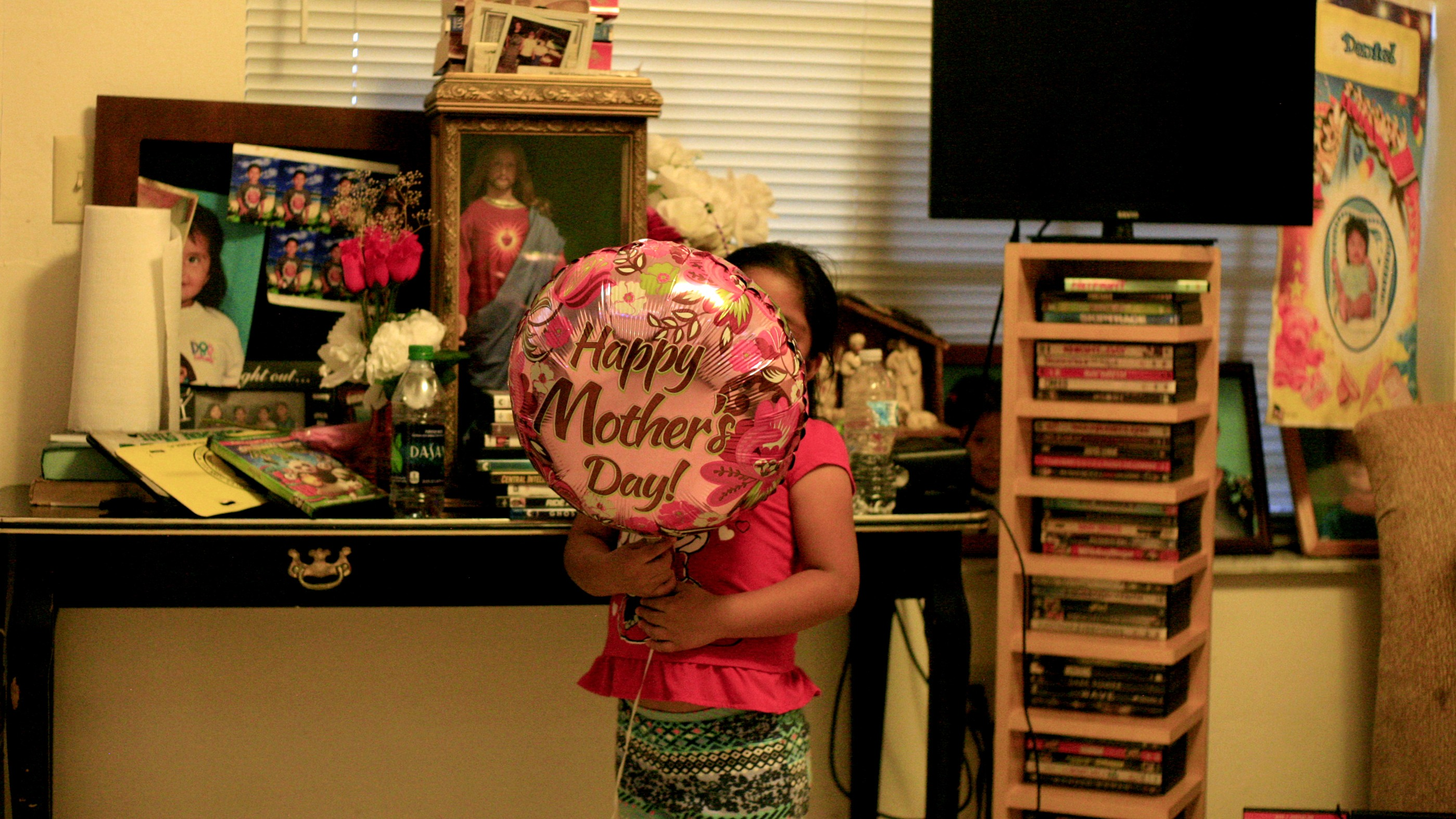 Girl in room with Mother's Day balloon in front of her face