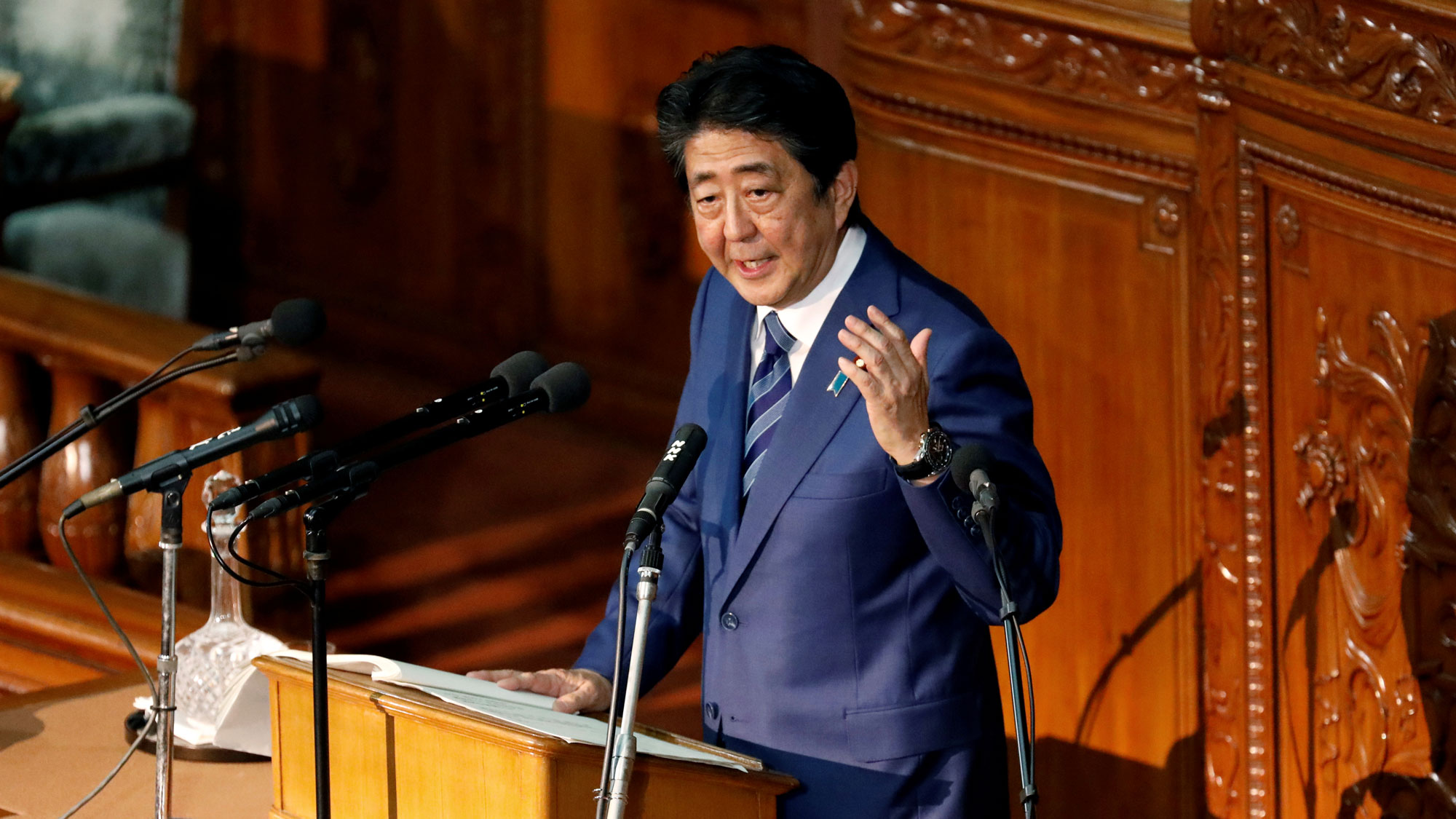 Japan's Prime Minister Shinzo Abe is shown standing at a podium with his left hand raised delivering a policy speech.