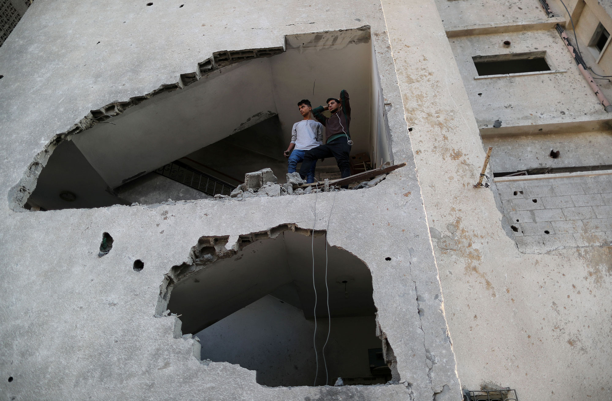 Palestinians look out of their house through a large hole in the wall created from an Israeli air strike.
