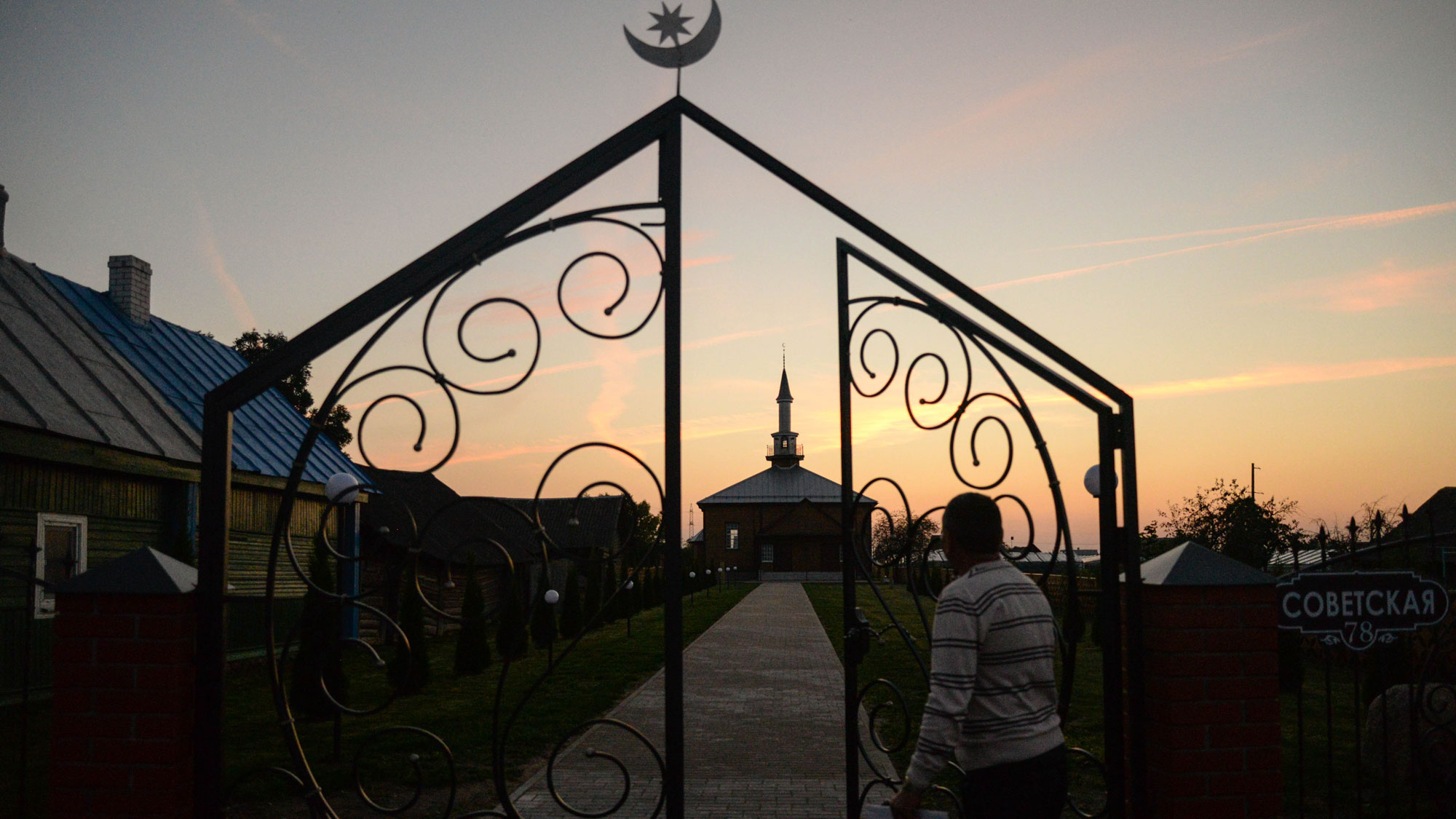 A sunset with the silhouette of a mosque and man approaching