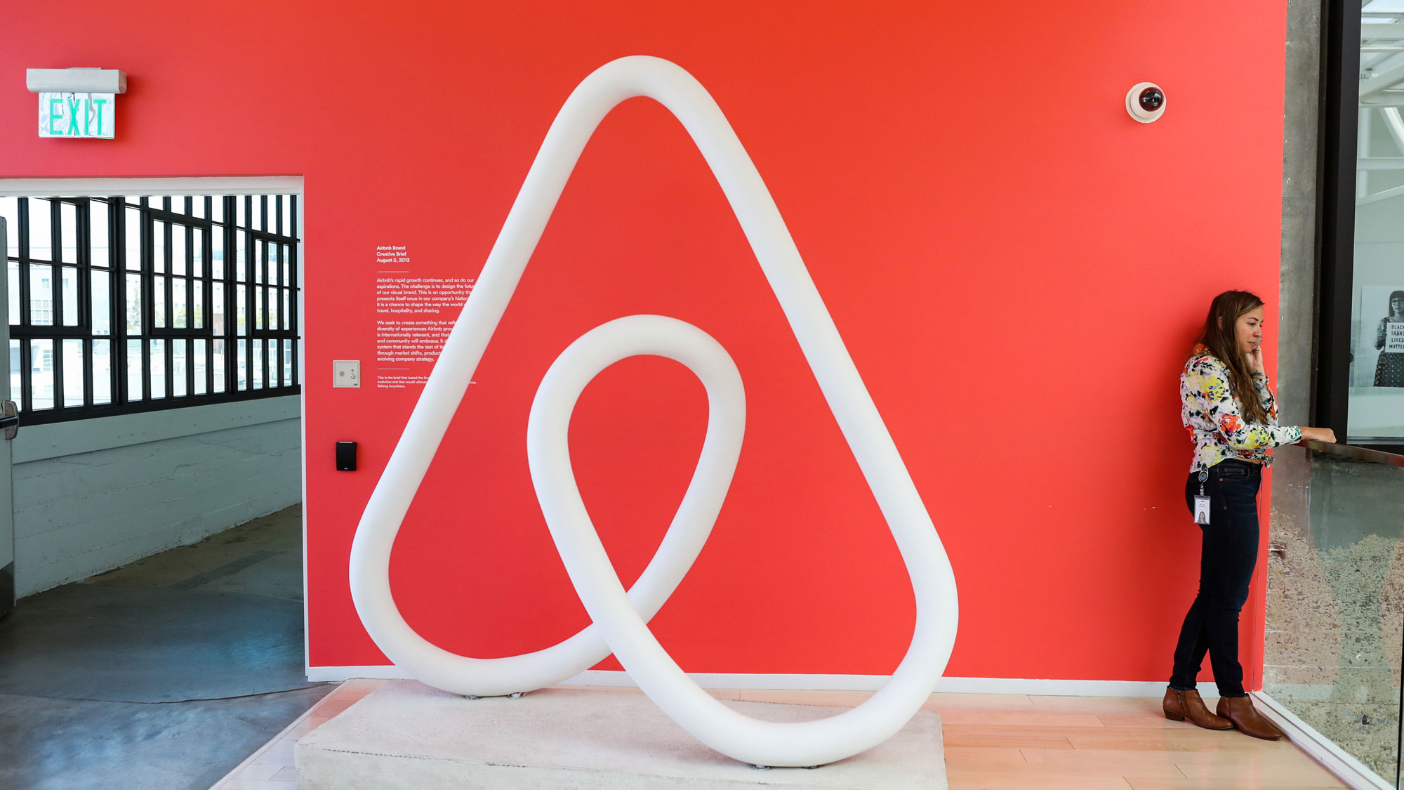 A woman is shown talking on the phone next to a red wall and a large sculpture of the Airbnb logo at the company's headquarters in San Francisco, California.