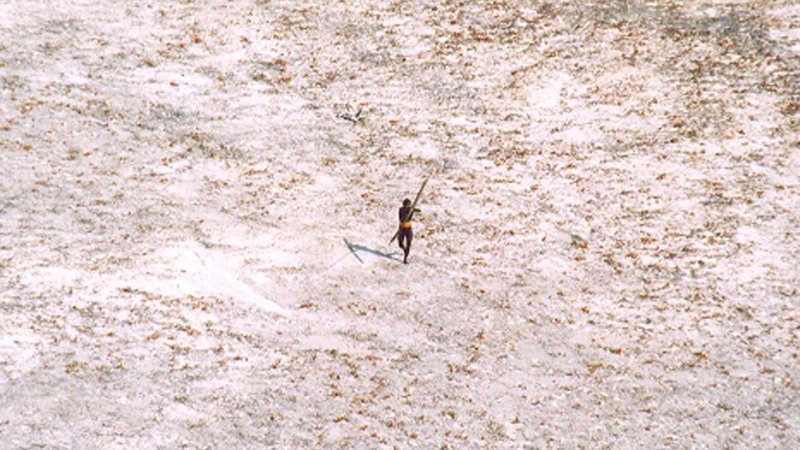 A man stands outside and aims his bow and arrow toward a helicopter.