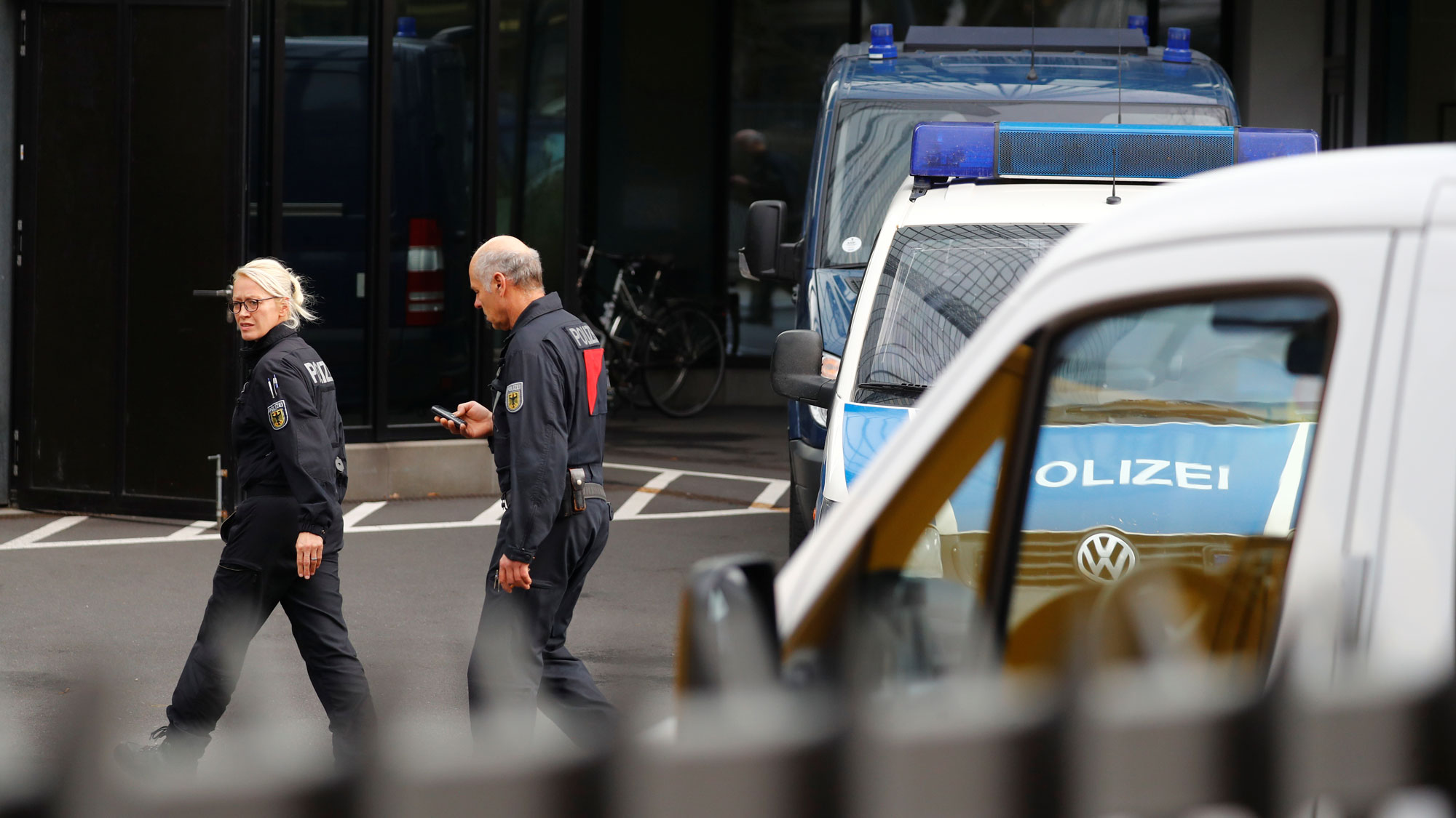 Two police officers are seen walking past police vehicles in front of Deutsche Bank headquarters in Frankfurt, Germany, Nov. 29, 2018.