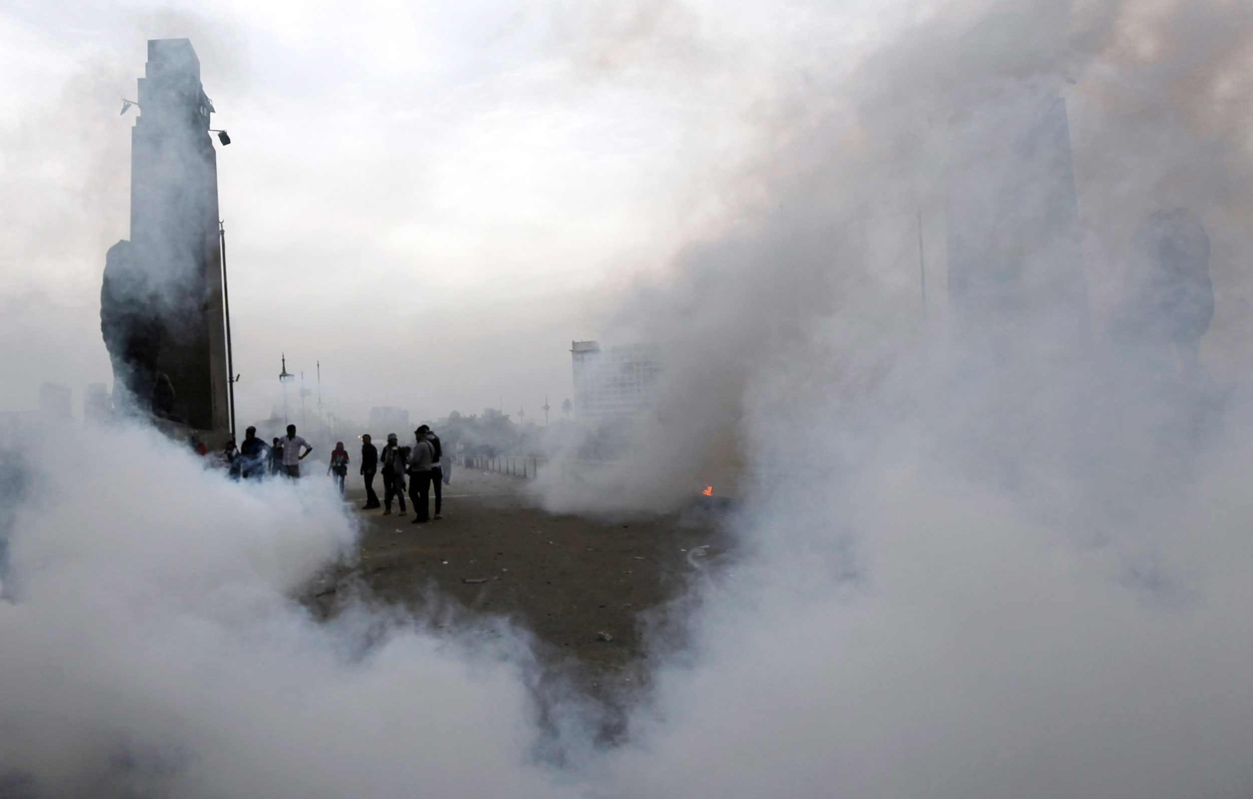 People stand surrounded by clouds of tear gas