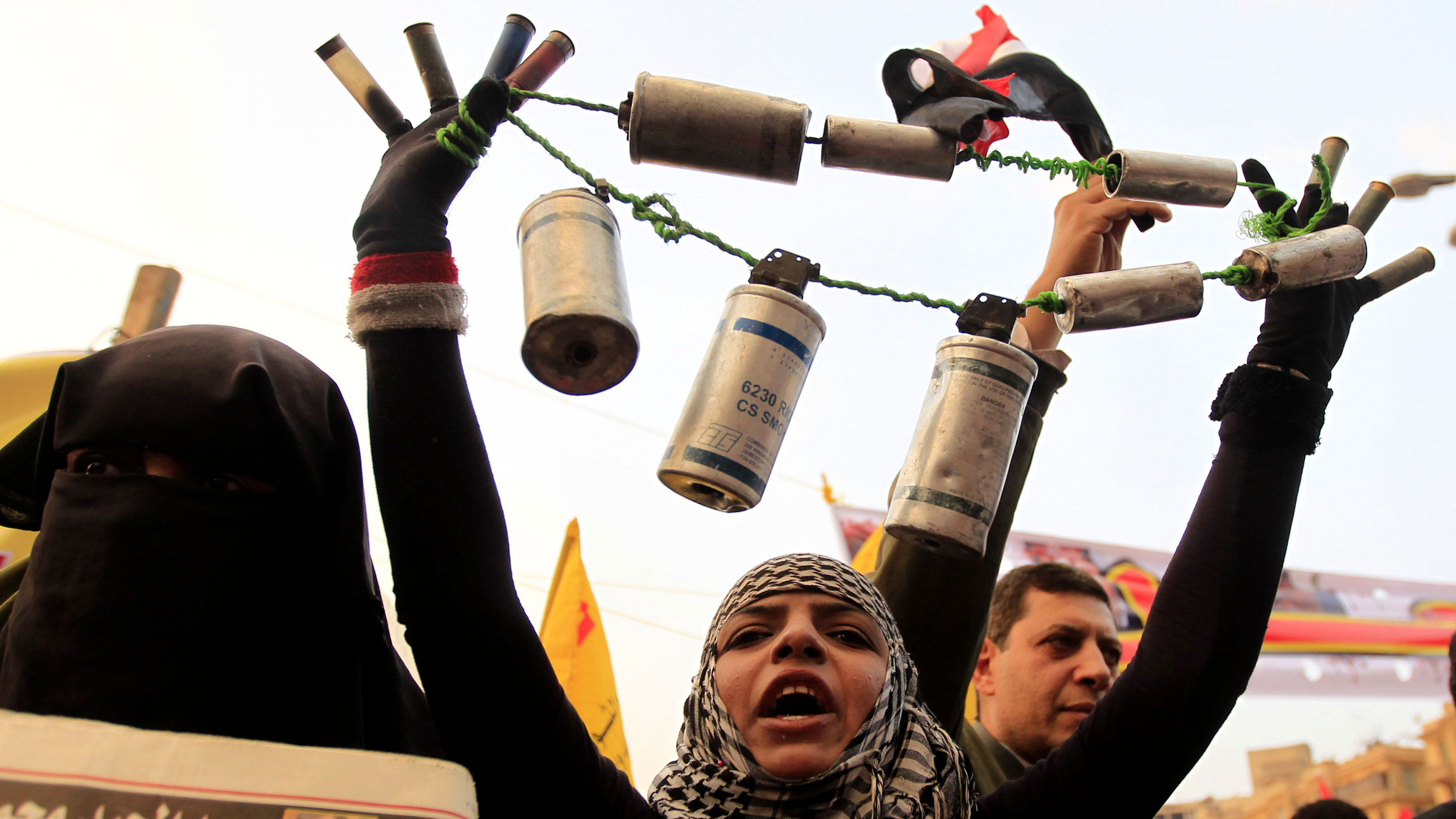 A person holds tear gas canisters and shot guns shells all tied on to a string