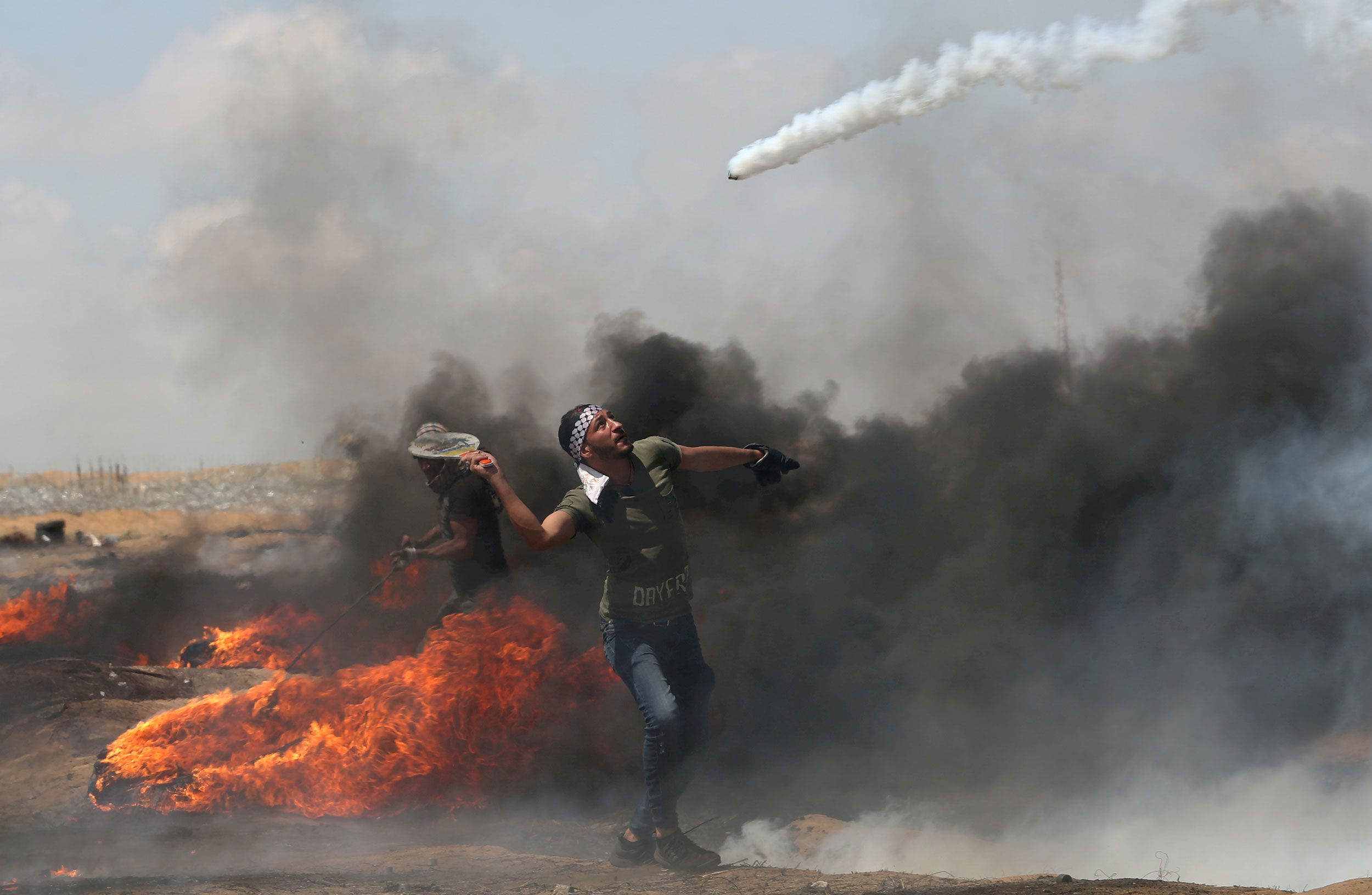 A man uses a racket to hit at a tear gas canister as it is launched through the air.
