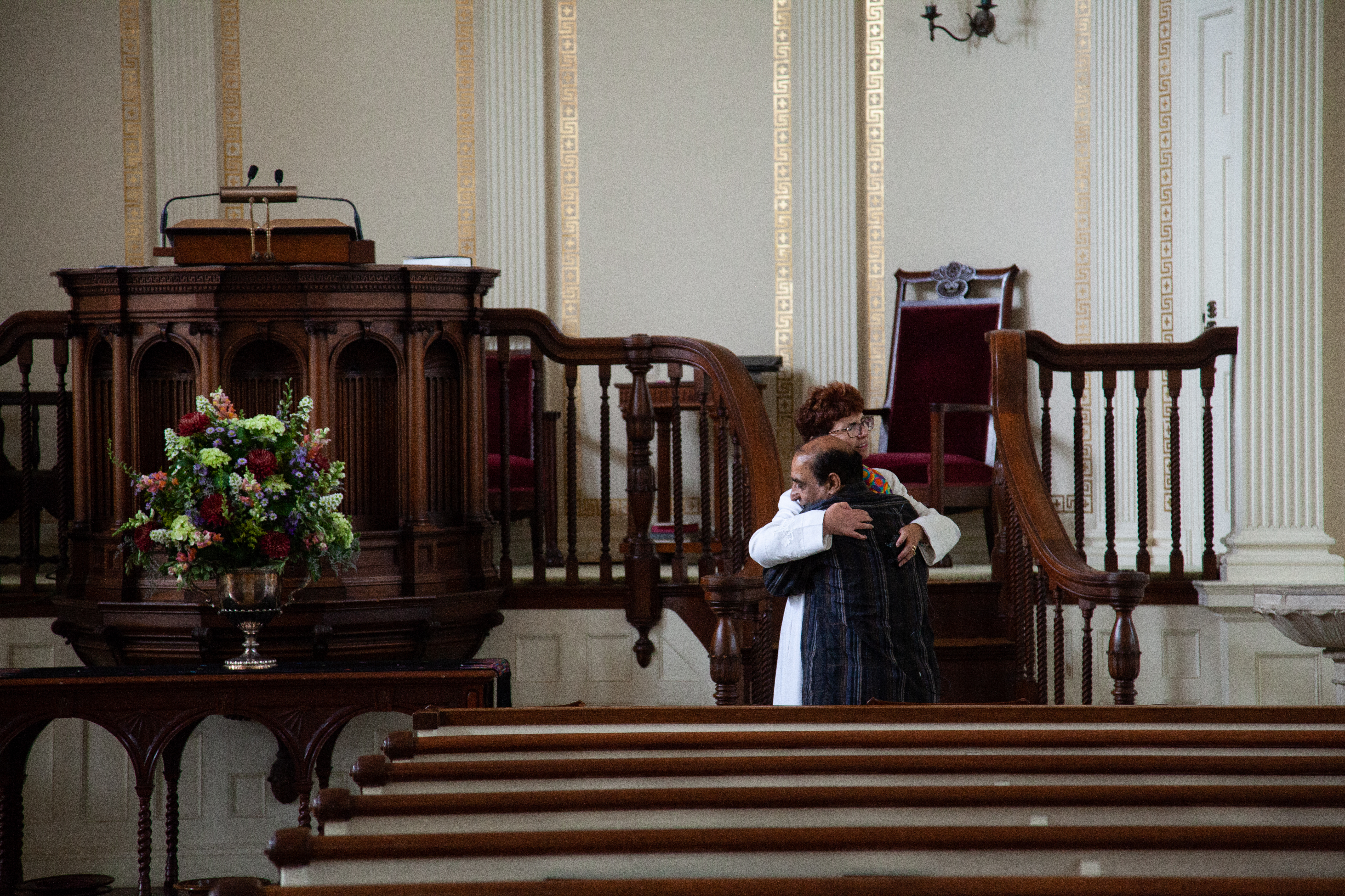 man hugging woman pastor in front of tall altar