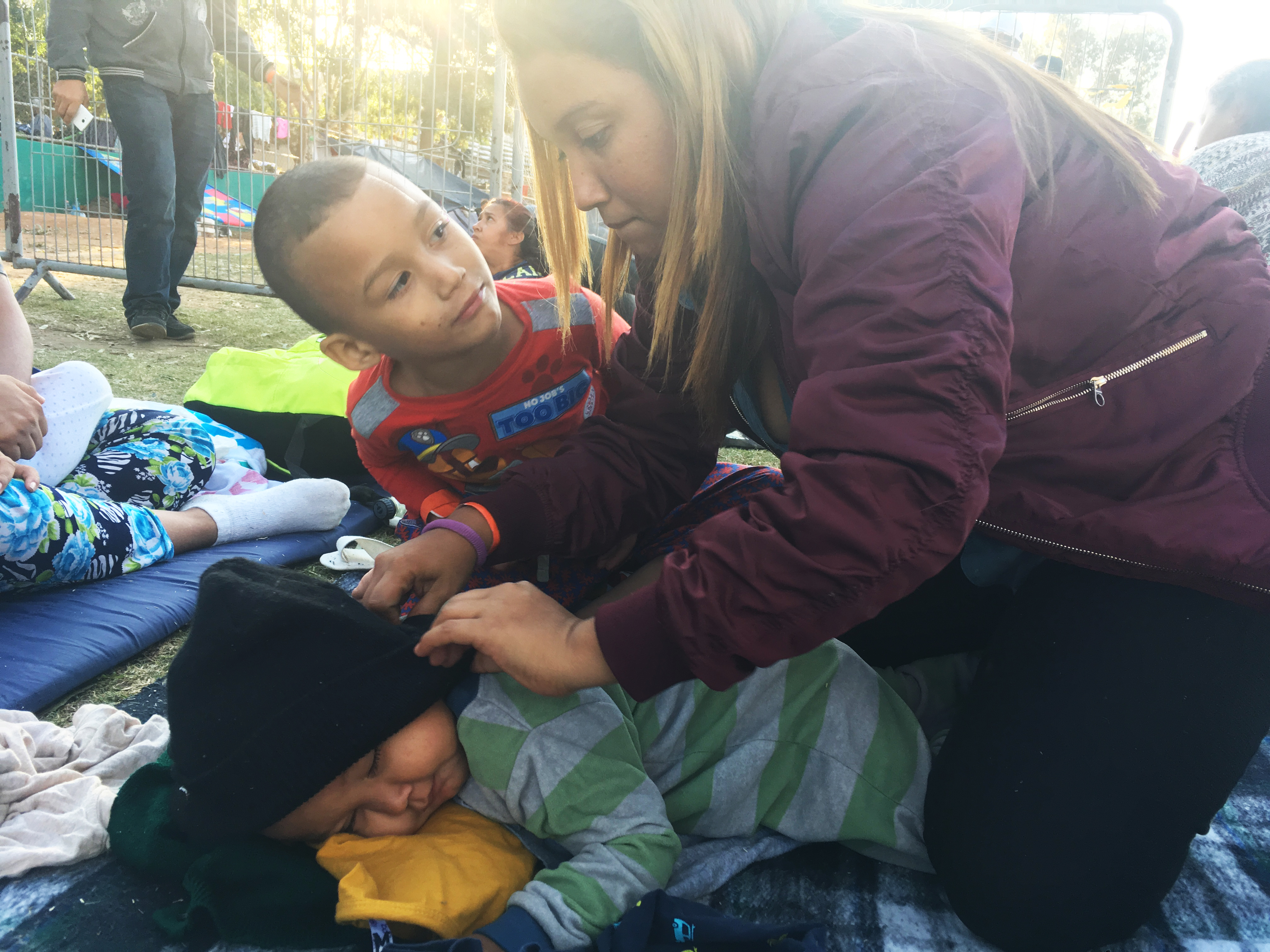 A woman covering her sleeping toddler with a coat