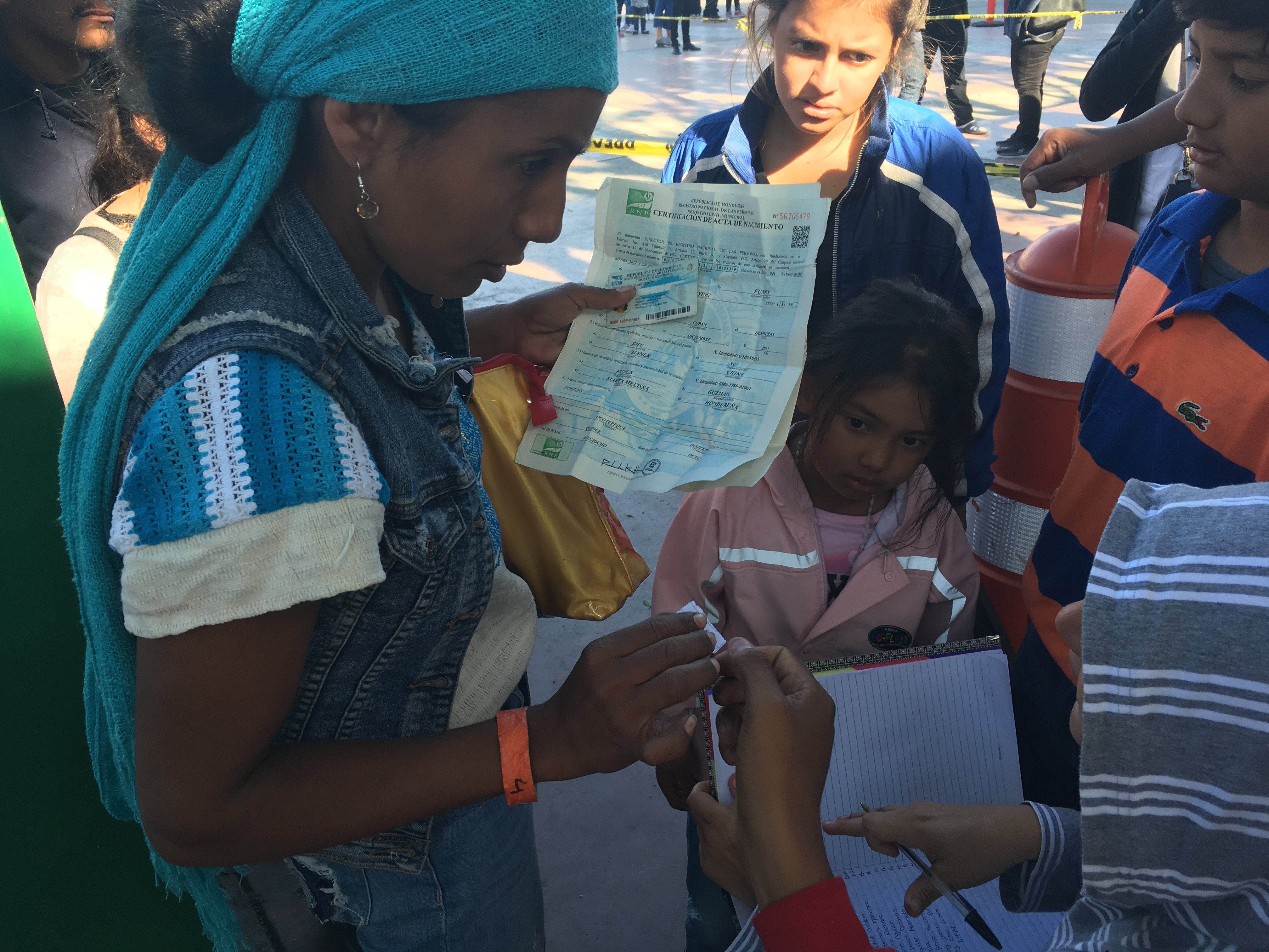 A mother and her kids registering their names in the notebook at the port of entry so they can get on the list to apply for asylum in the US.