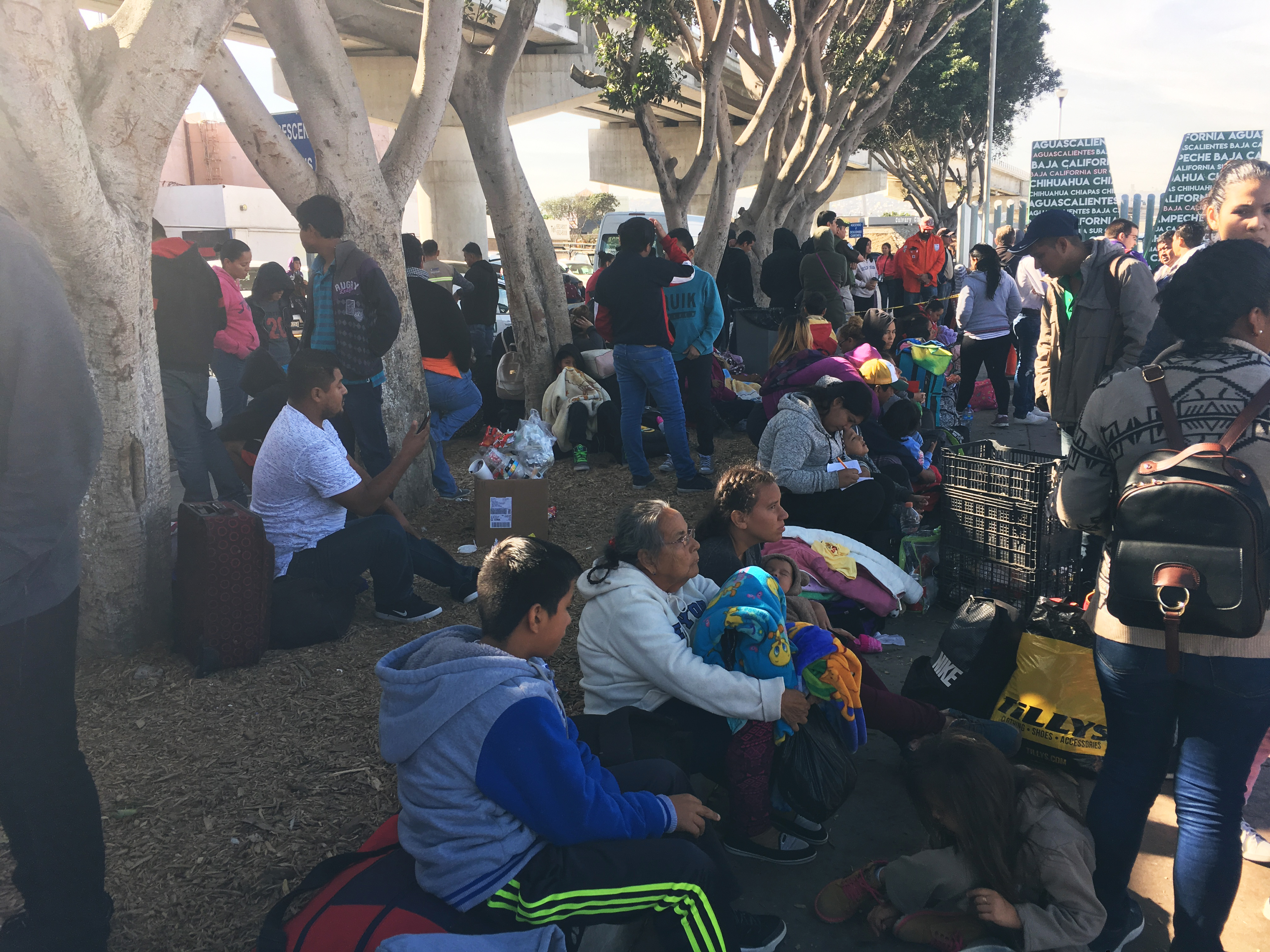 Families wait outside the port of entry to see where the are on the list, and when they can apply for asylum
