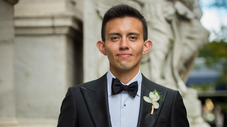 Man posing for camera, wearing suit