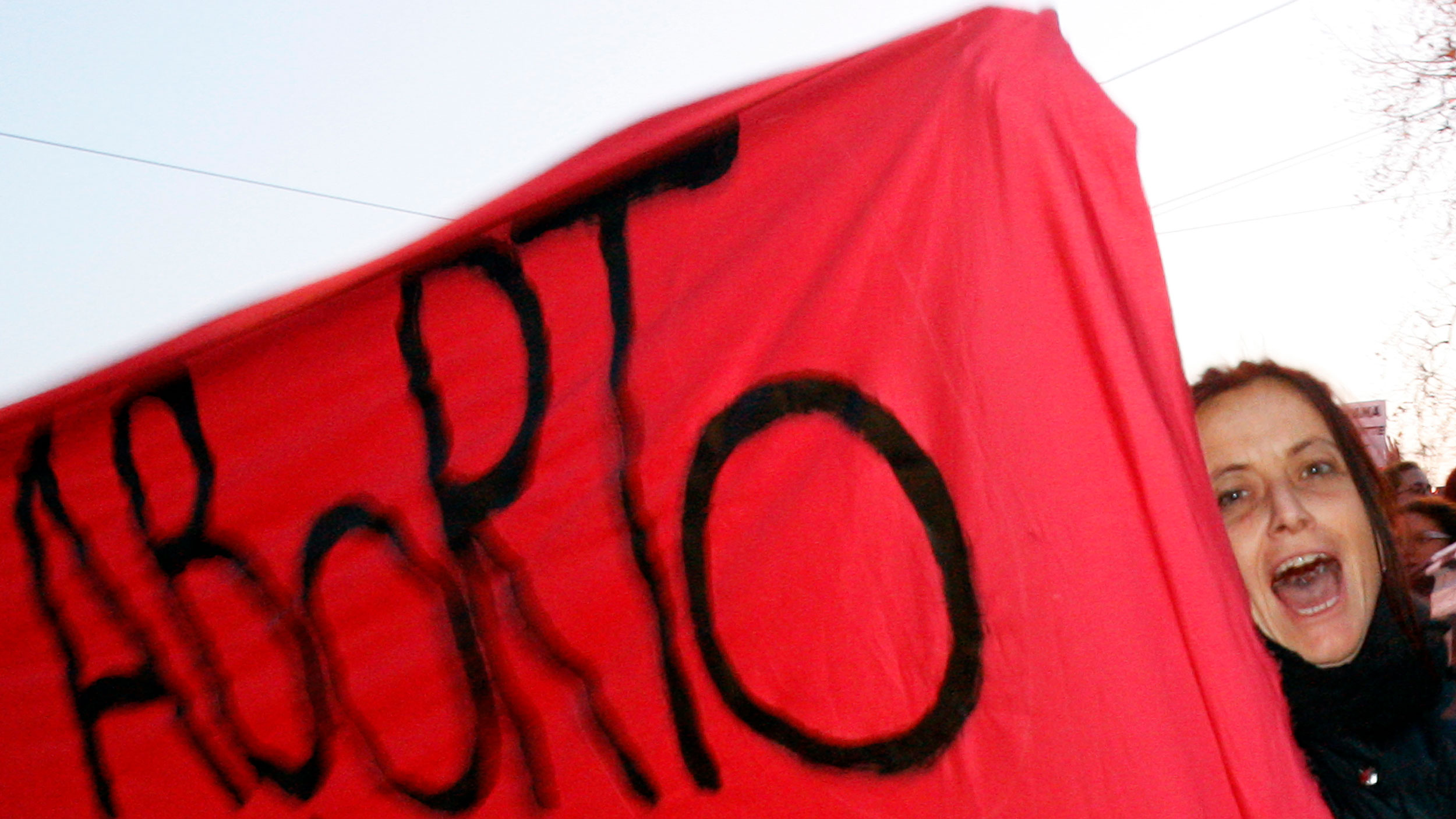 "A woman's face looks out from behind a red protest banner that says ""aborto"""