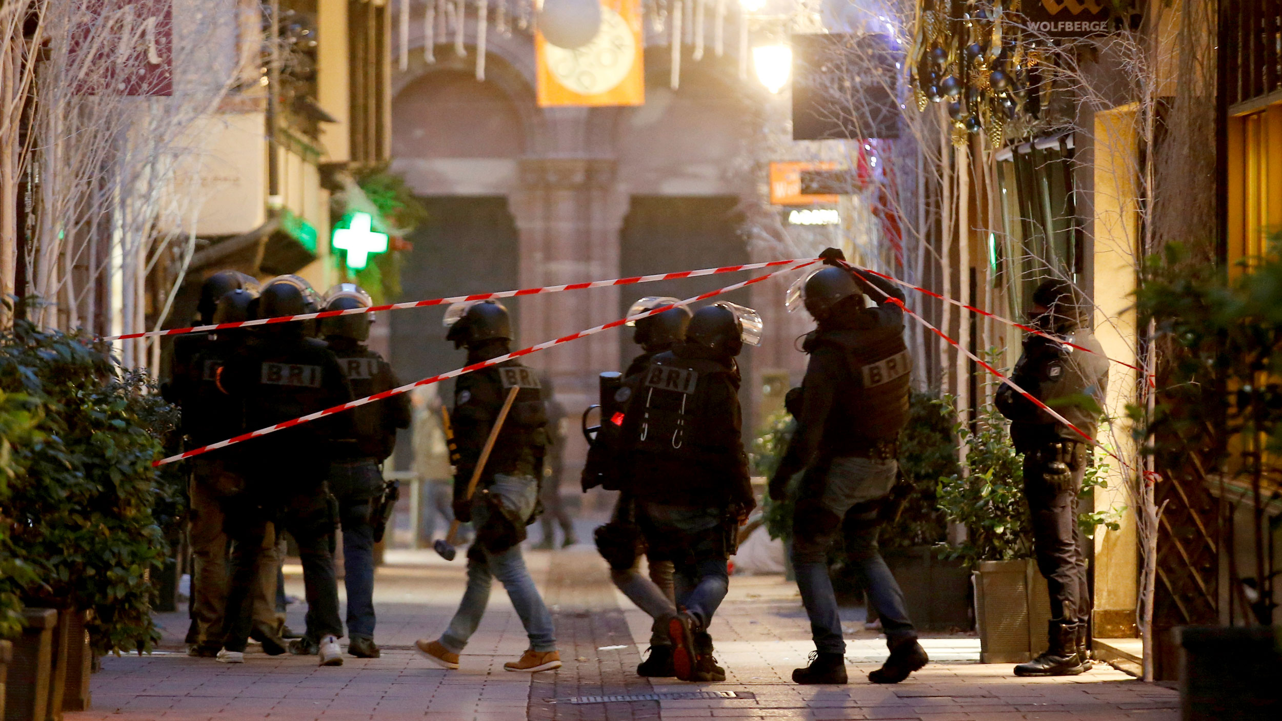 Police in riot gear lift a red tape to enter a crime scene