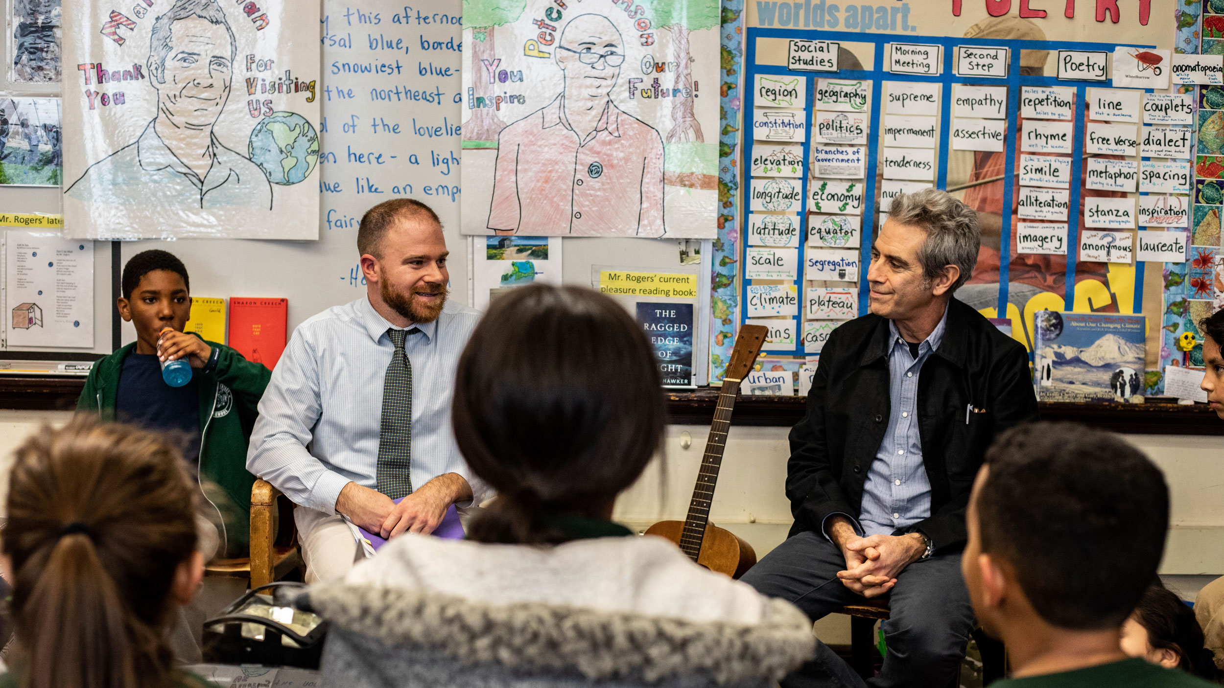 Two adults sit at the front of an elementary school classroom as children's heads fill the bottom of the frame.