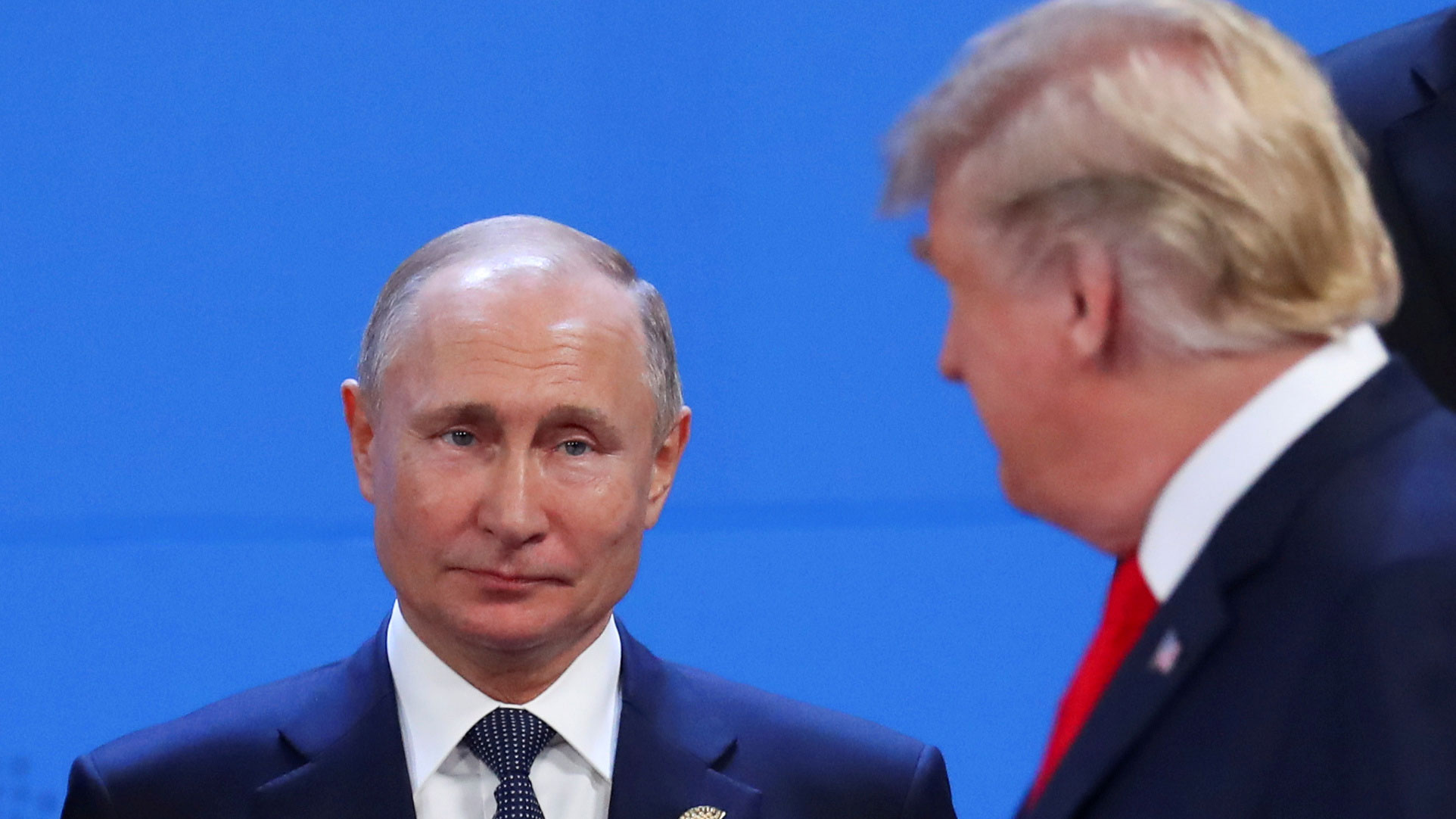 US President Donald Trump is shown out of focus in the near ground with Russia's President Vladimir Putin seen in focus in the background.