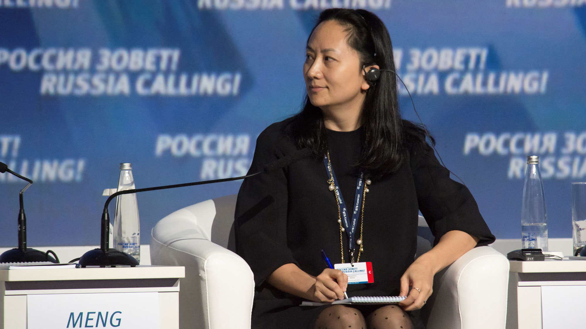 """Meng Wanzhou, wearing all black, is shown seated with a pen and notepad at a session of the VTB Capital Investment Forum """"Russia Calling!"""" in Moscow, Russia, 2014."""