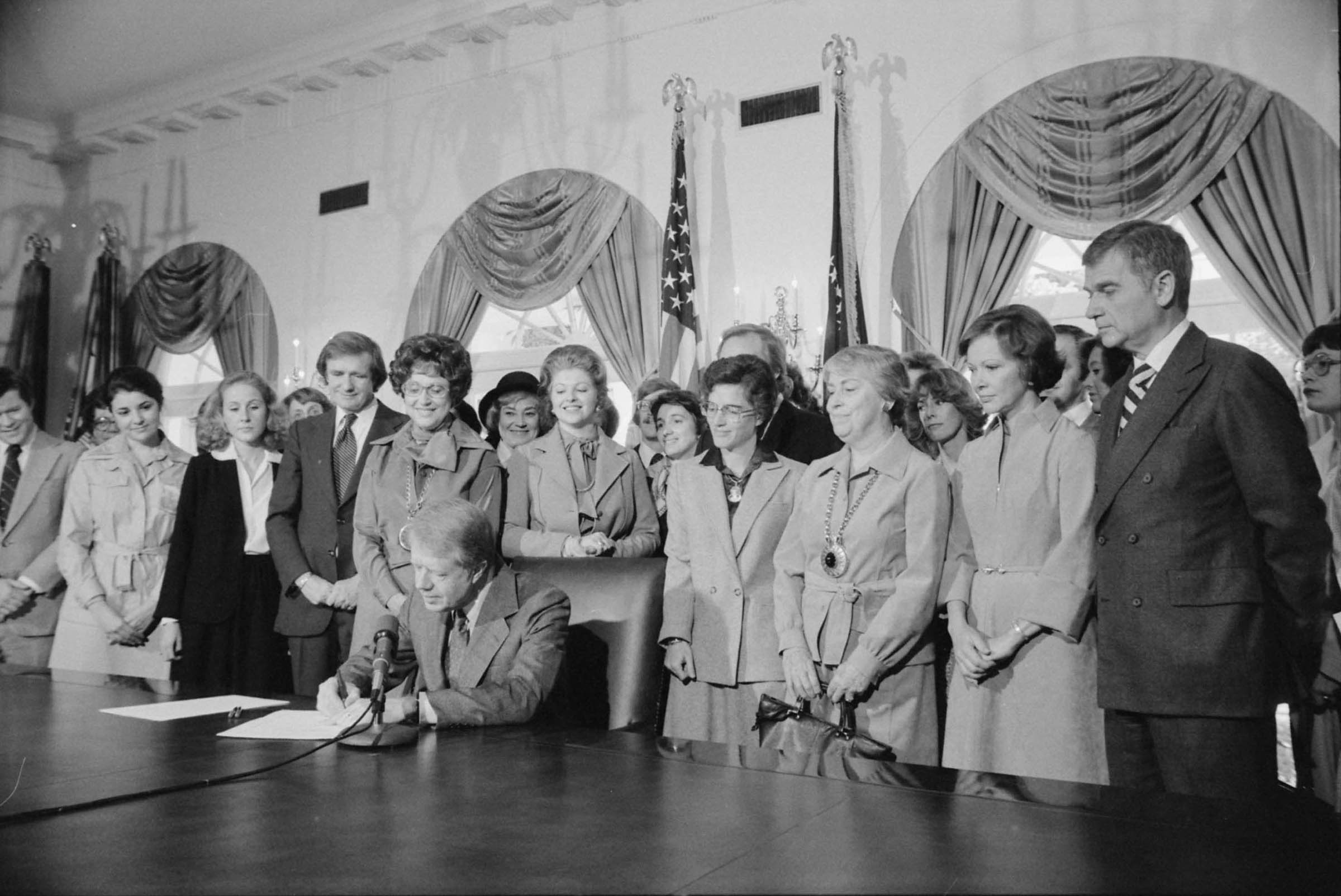 Jimmy Carter sitting down with several women standing behind him