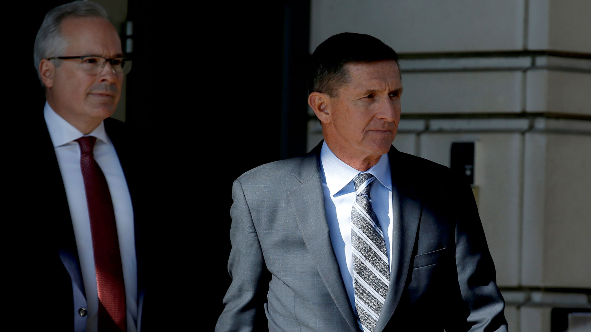 Former US National Security Adviser Michael Flynn is shown departing US District Court wearing a grey suit and striped tie.