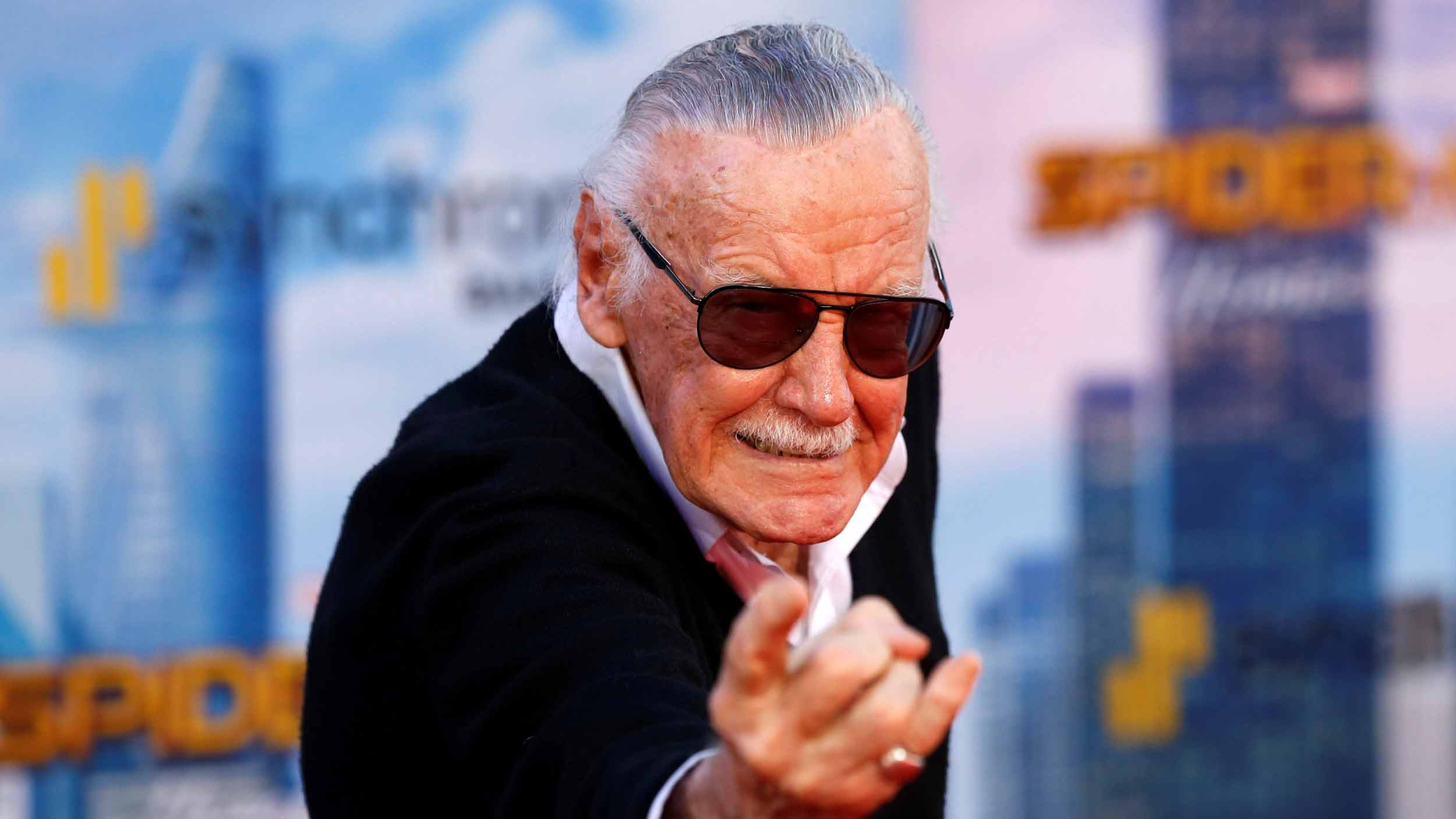 Stan Lee poses like Spiderman shooting a web from his wrist