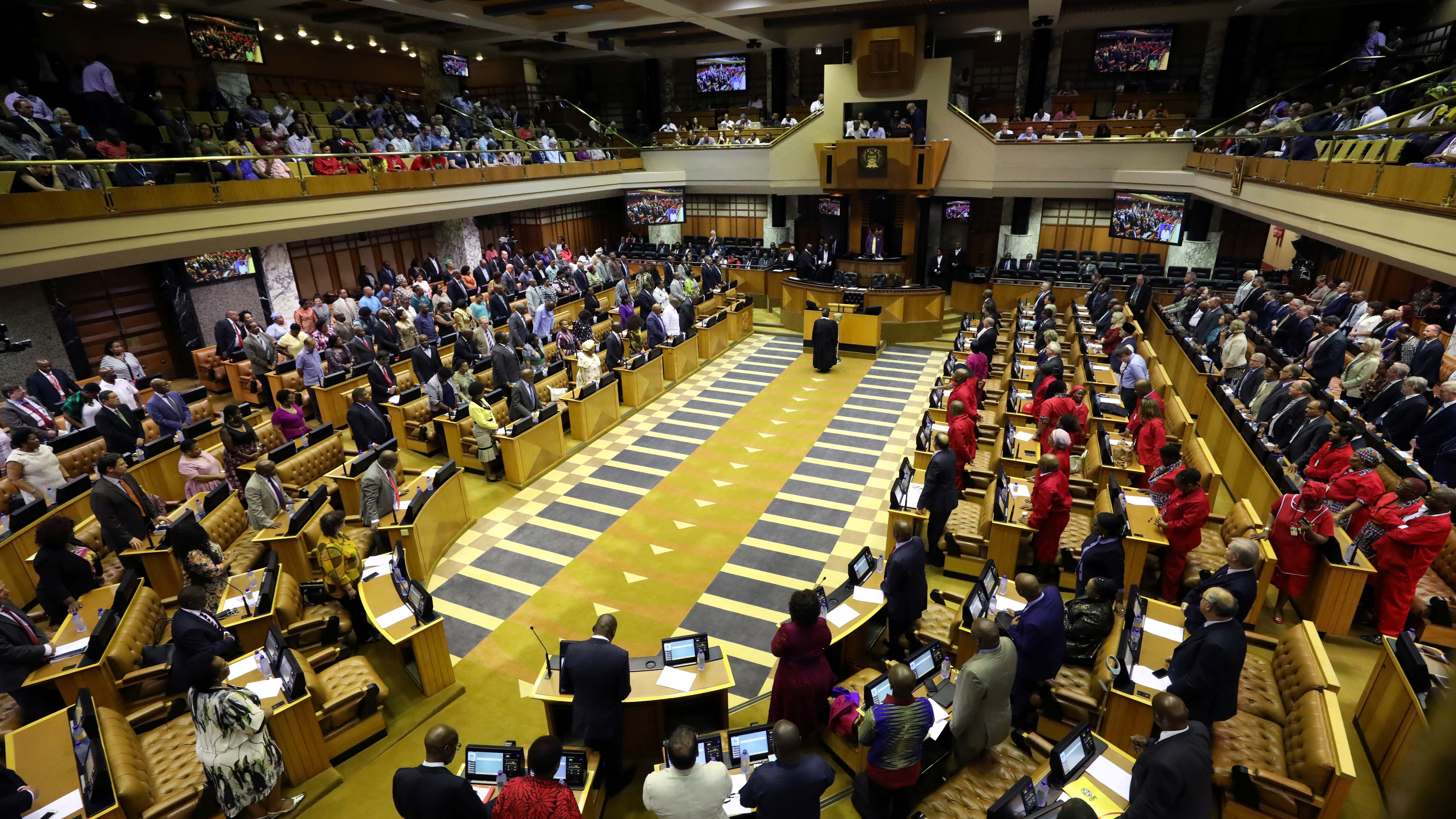Members of parliament from a top-down view with a podium in the center