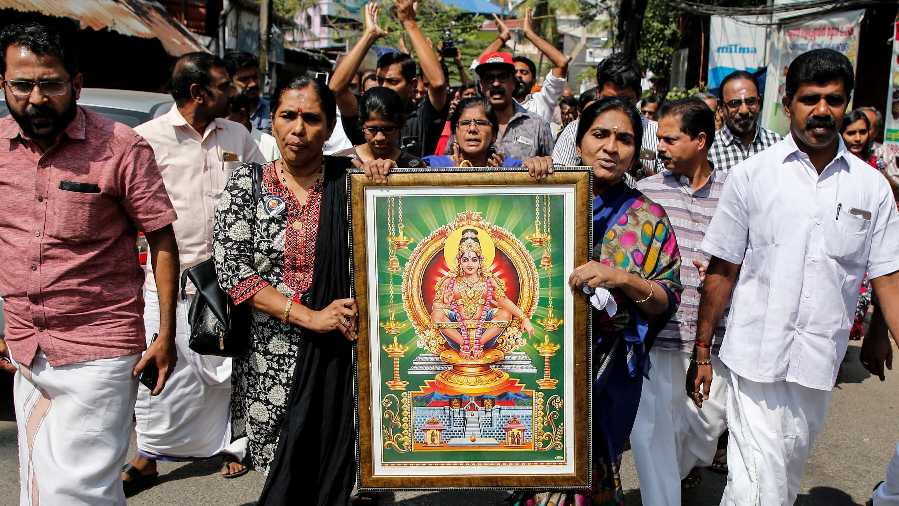 Protesters walk down the street carrying a sign of a Hindu deity.