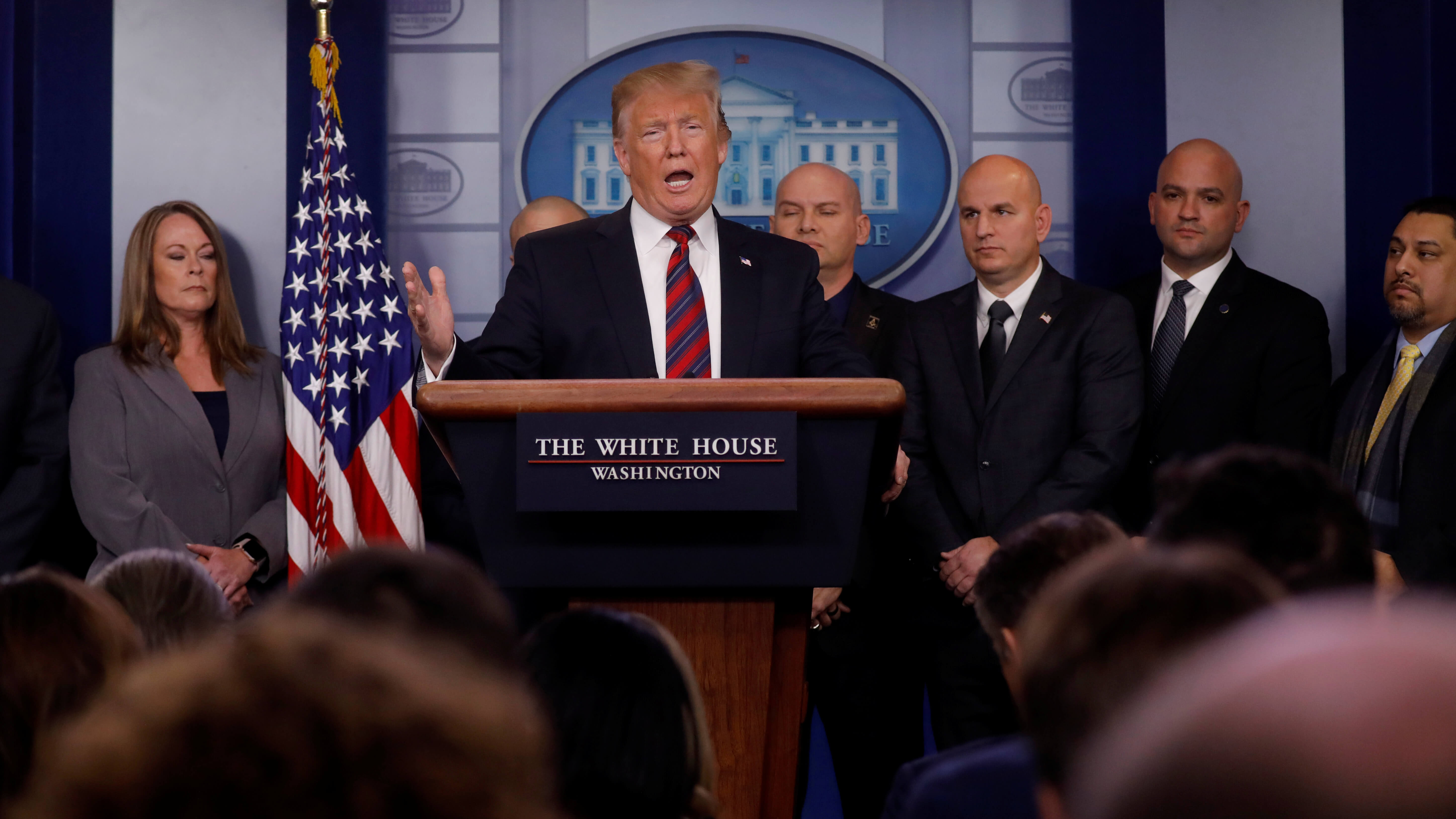 President Trump speaks at a podium while 3 bald men stand behind him.