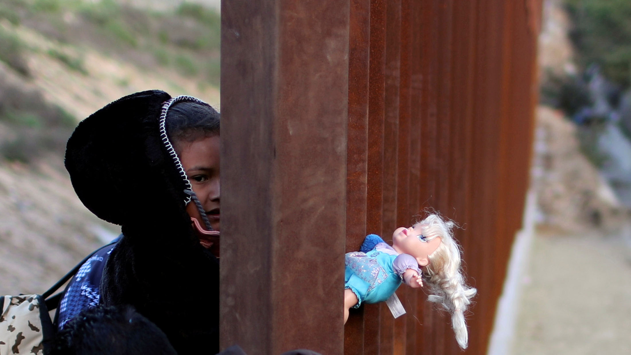 a little girl and her doll peek through a rusted wall
