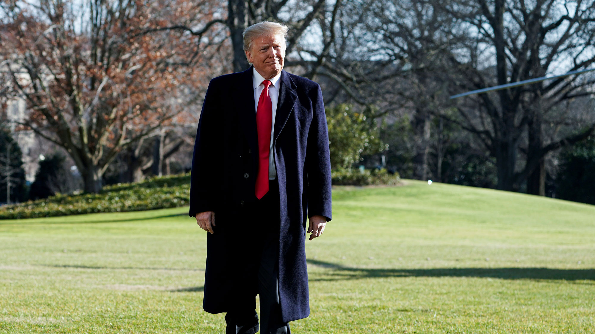 US President Donald Trump is shown walking on a grassy lawn with a dark overcoat on.