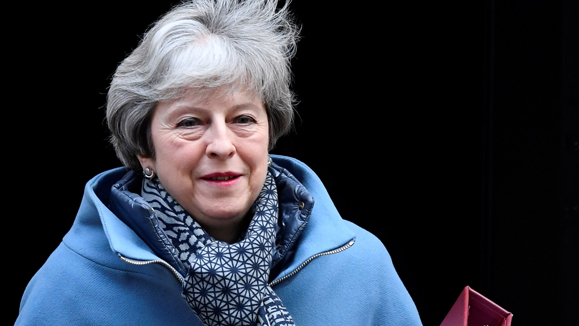 Britain's Prime Minister Theresa May shown leaving Downing Street wearing a blue jacket and scarf while carrying a red binder.