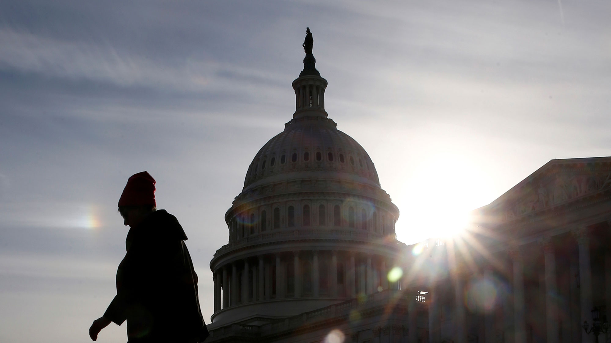 A person is shown in shadow, backlight by a bright sun walking by the US Capitol.