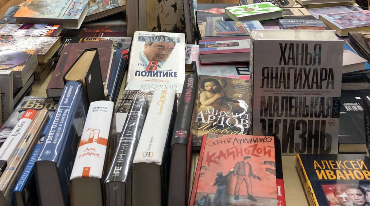 Dozens of books in Russian are on display on a table inside a bookstore.