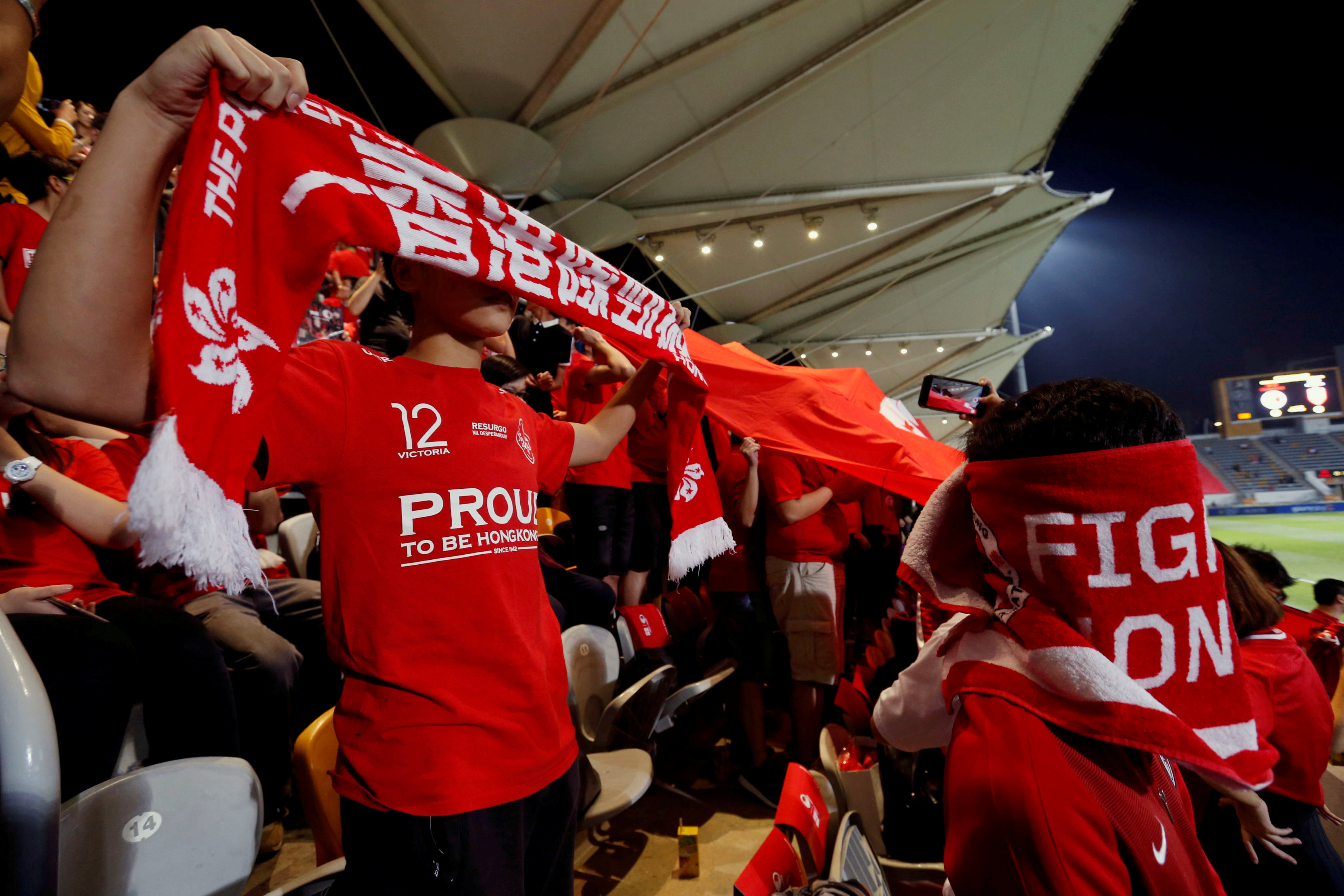 Hong Kong fans cover their faces and boo during the Chinese national anthem, at a friendly soccer match between Hong Kong and Bahrain in Hong Kong, China, November 9, 2017.