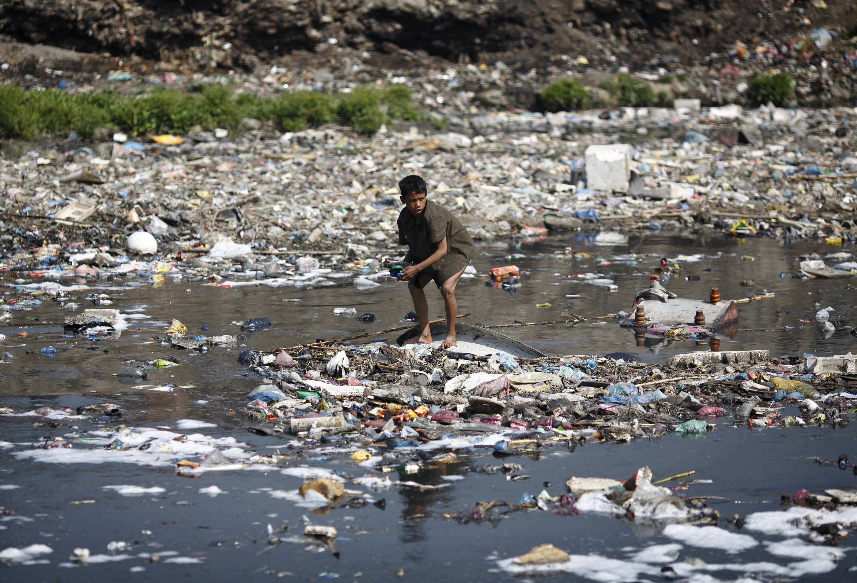 A boy crouches on an island of plastic.