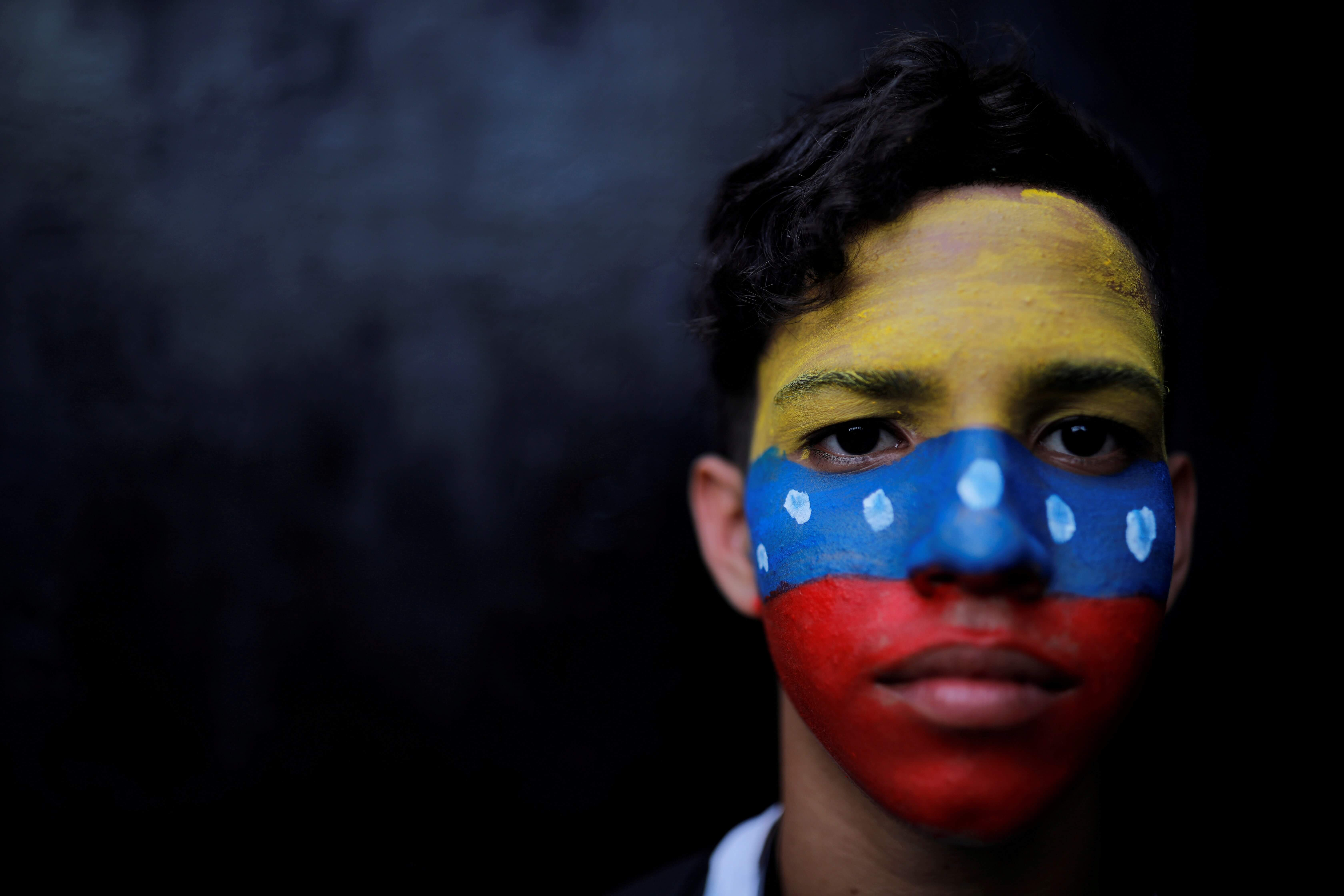 a closeup of a young boy with the Venezuelan flag painted on his face