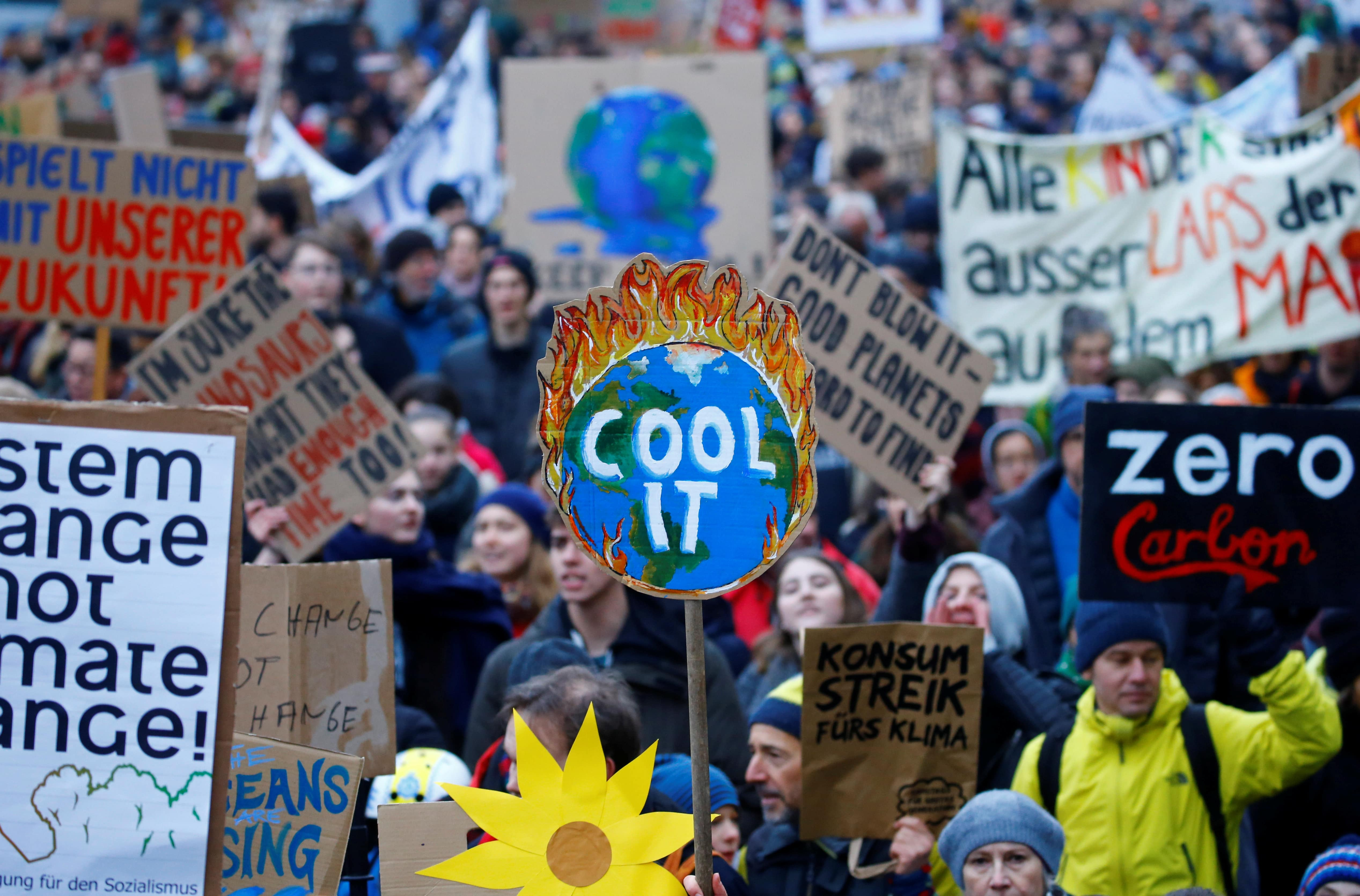 """a large crowd of people marching, a sign that read """"cool it"""" is the most prominent"""
