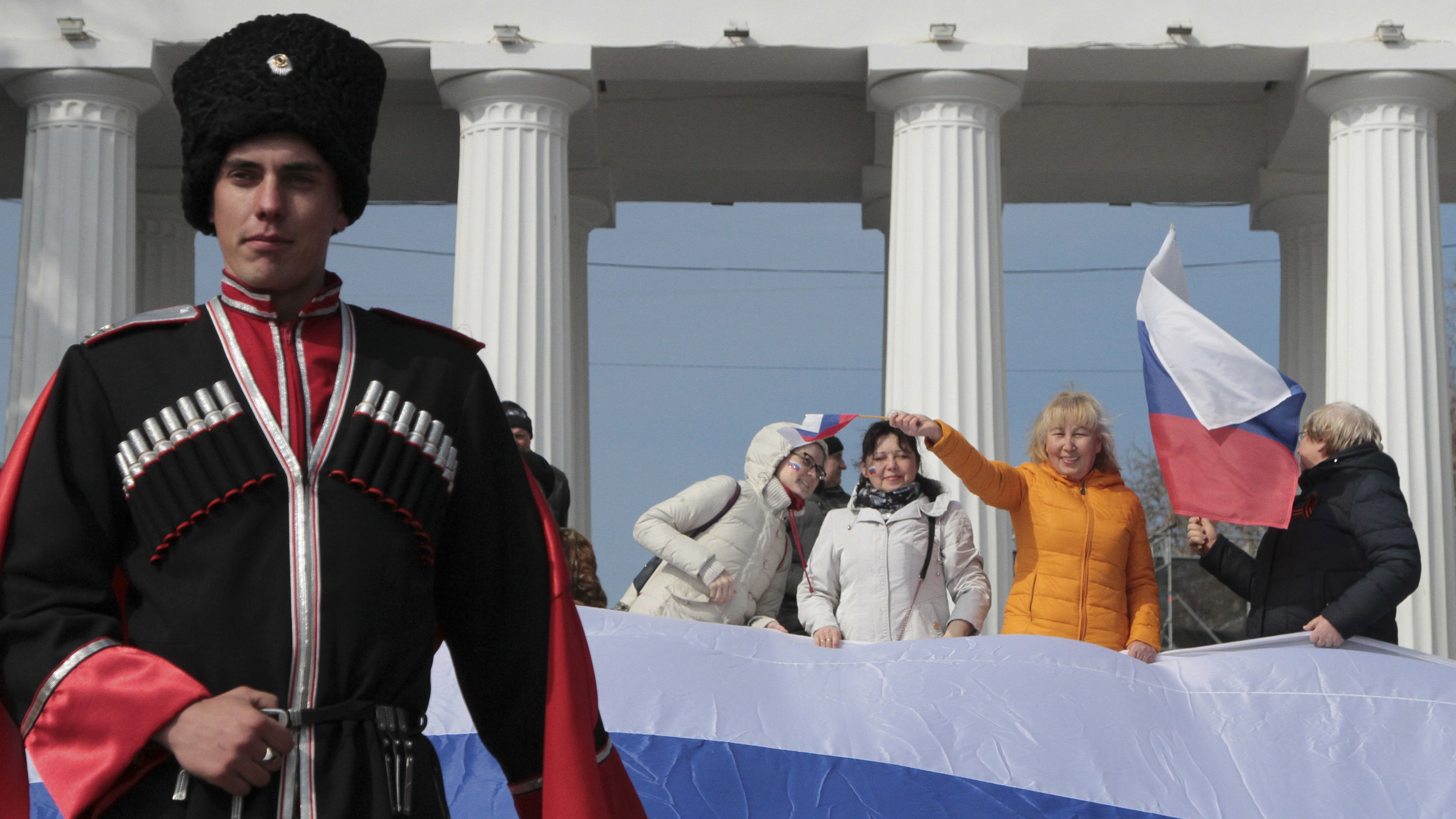 A Russian soldier stands in the foreground of citizens celebrating, waving flags